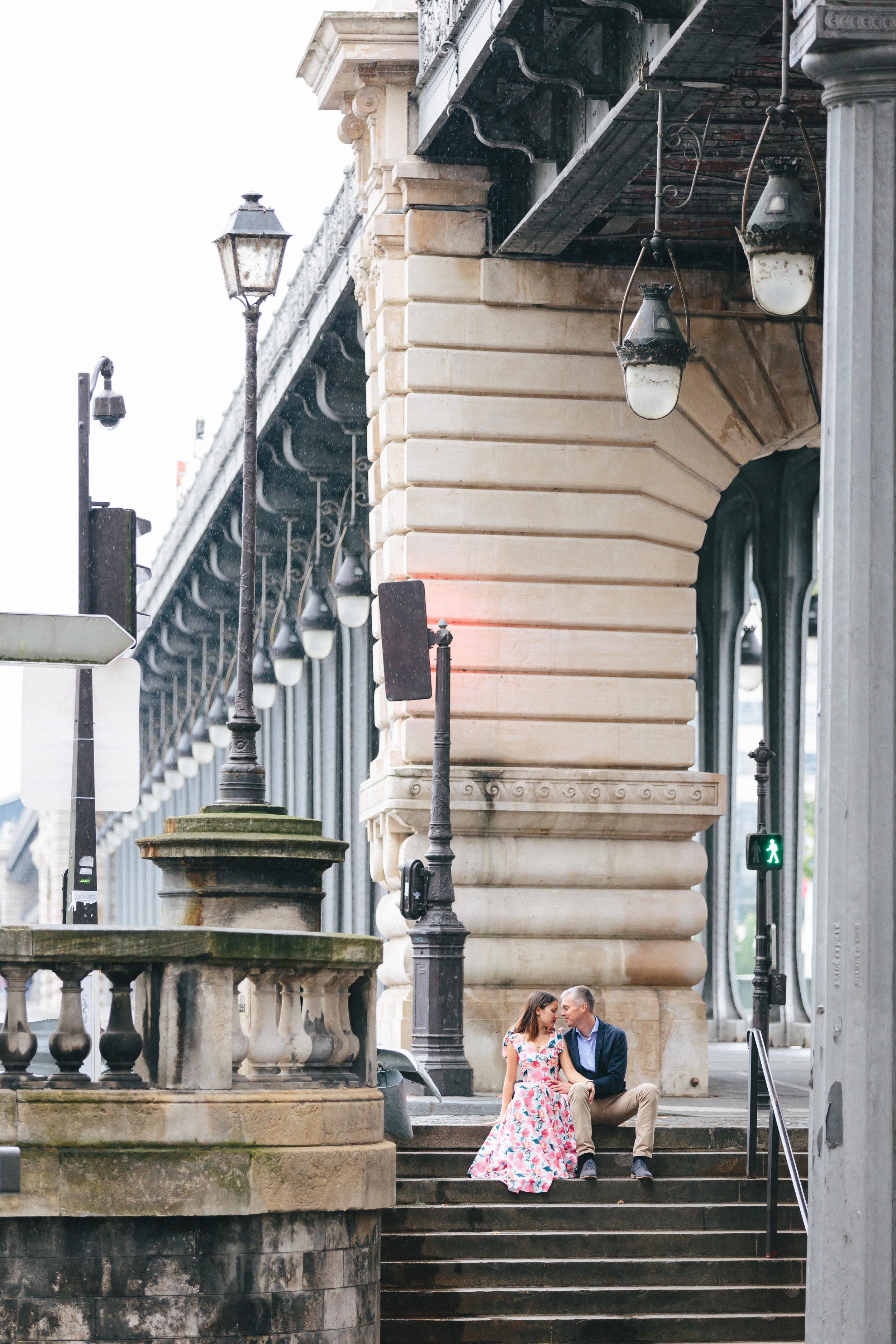 romantic couple portrait sitting at the steps of bir hakeim bridge by paris photographer federico guendel