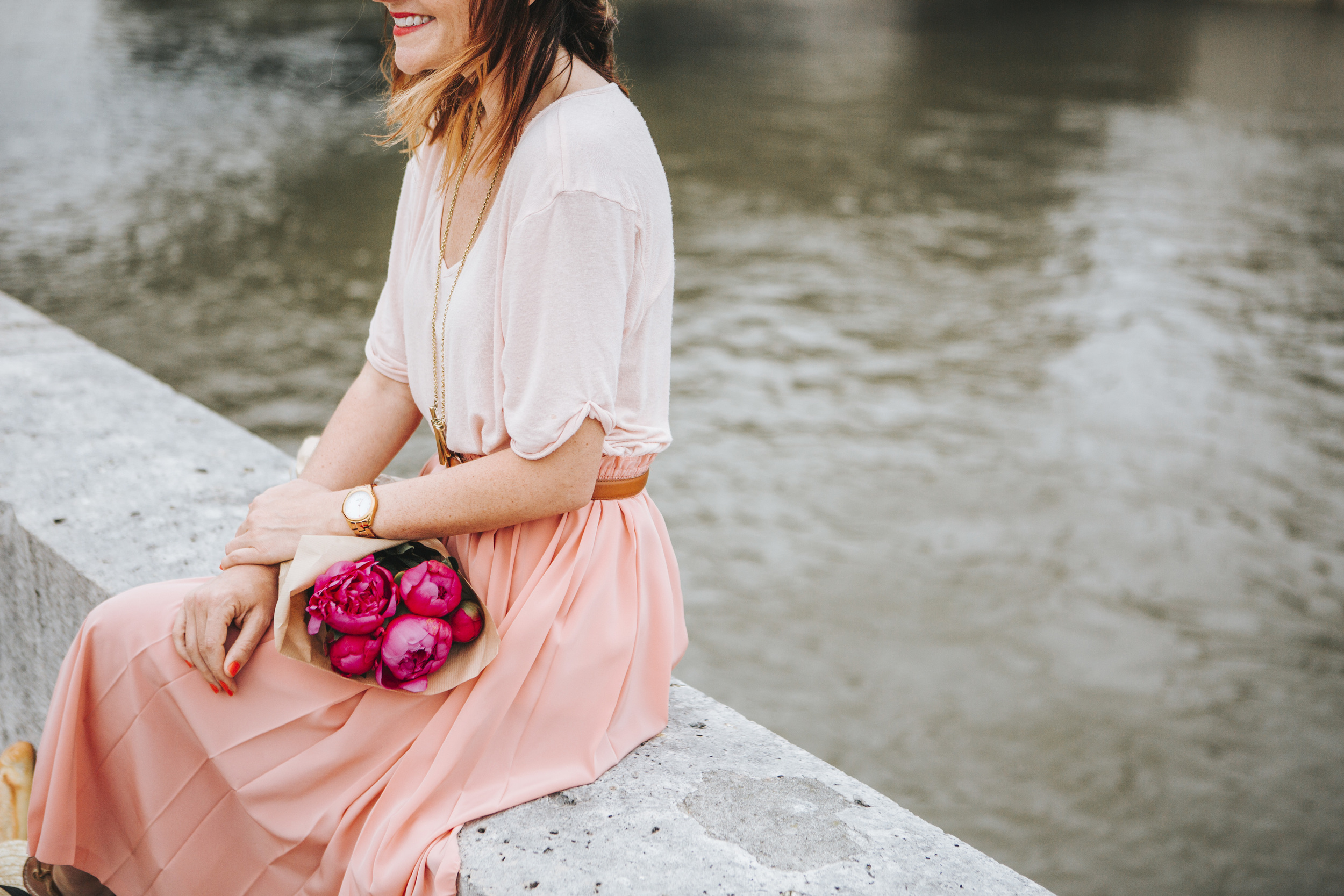 paris photographer fashion blogger lifestyle portrait by the seine river with bouquet of peonies