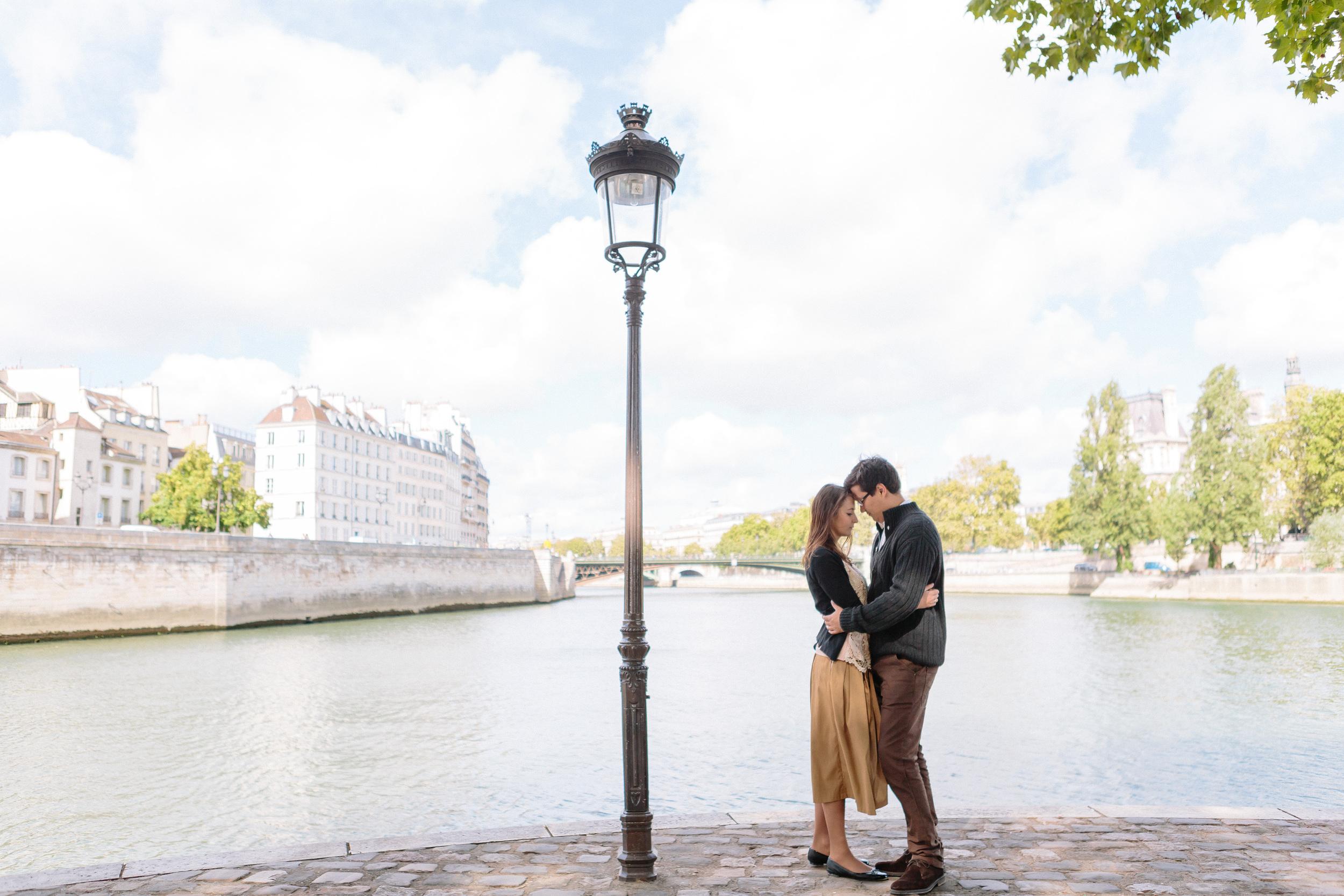paris photographer engagement couple portrait by lamp post at ile saint louis by the seine river