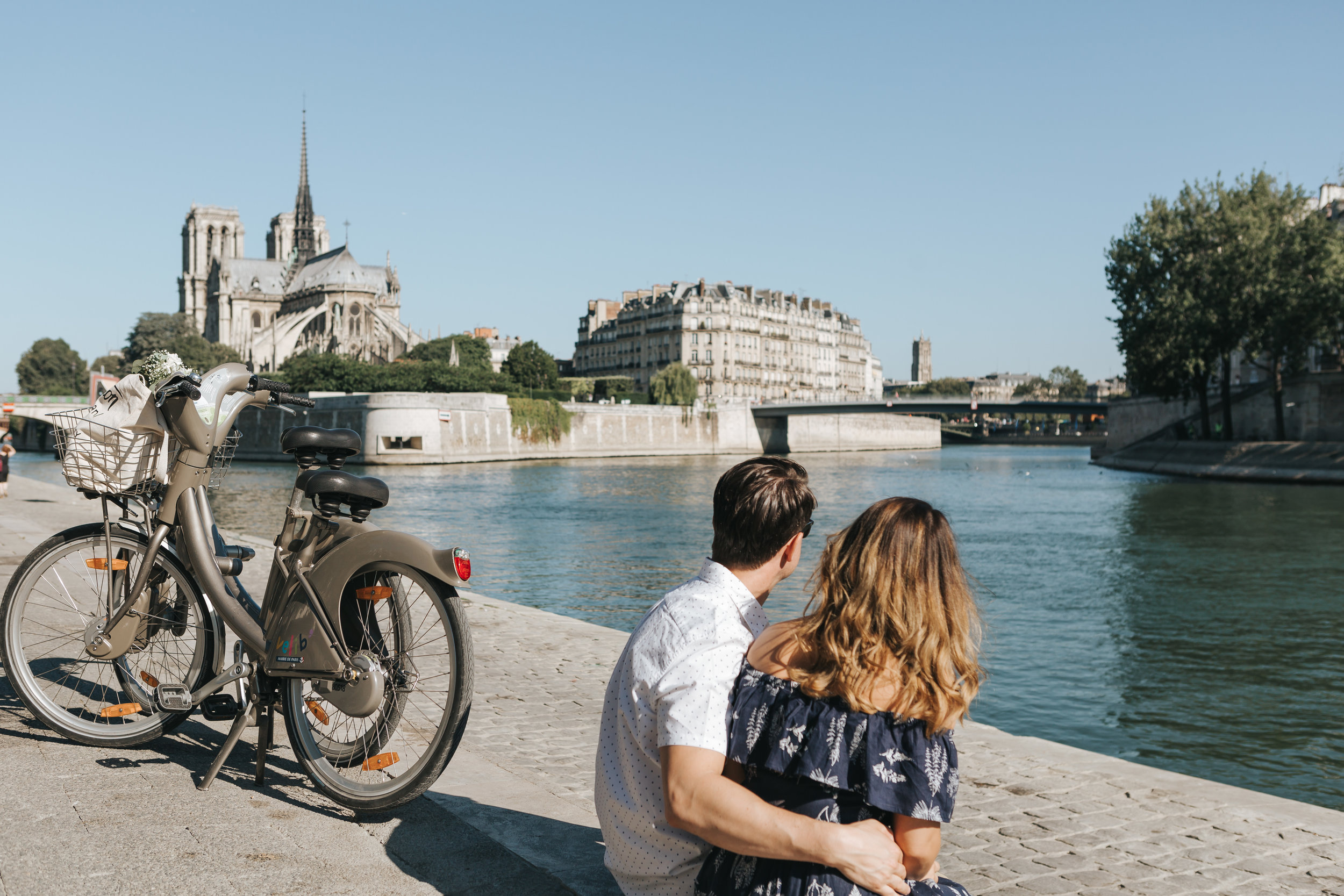 paris photographer anniversary couple session by seine river with bicycle near notre dame