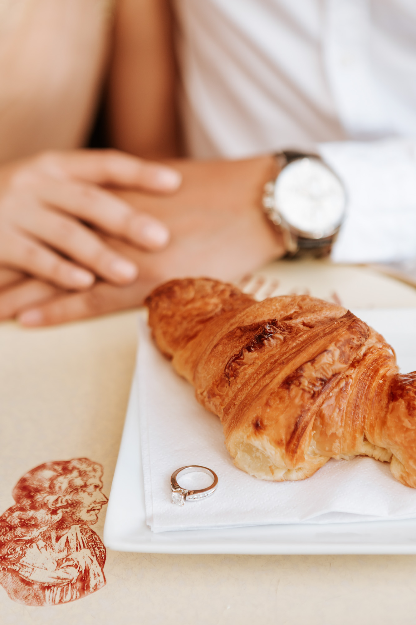Pre-wedding diamond engagement ring next to coffee and croissant at cafe captured by Paris Photographer Federico Guendel