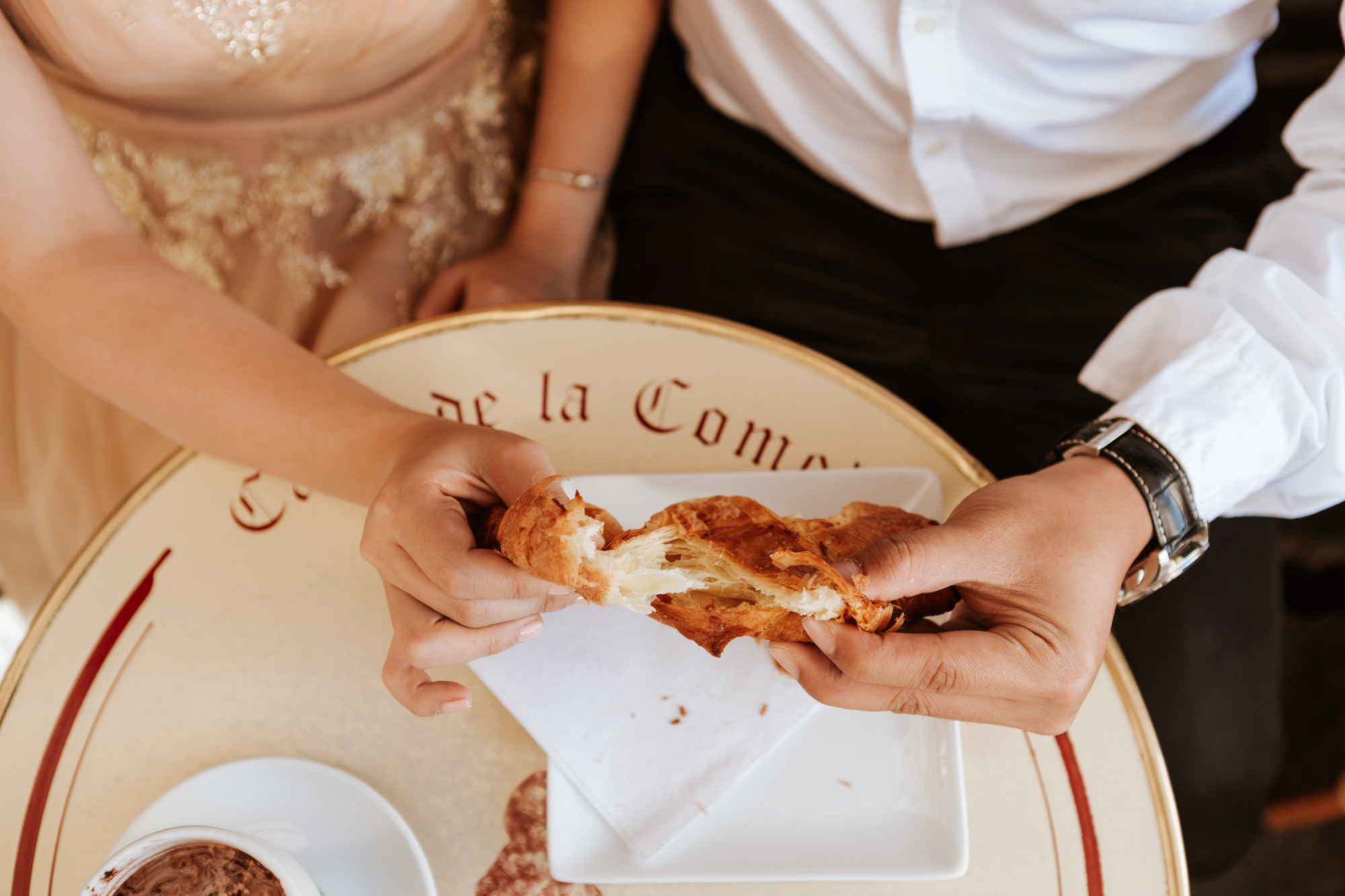 Cafe de la comedie couple pre-wedding photo session sharing croissant captured by Photographer in Paris Federico Guendel