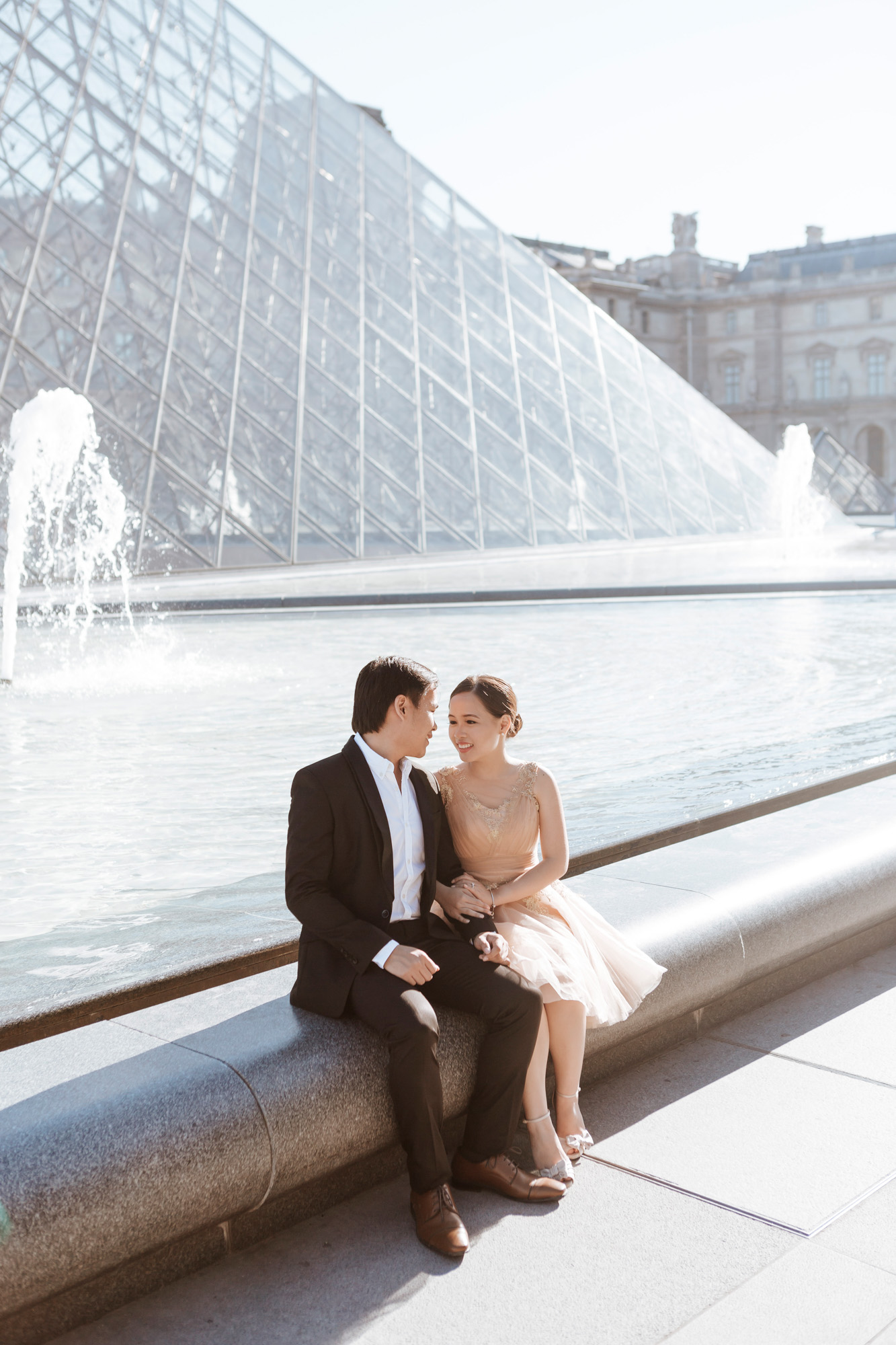Pre-wedding couple portrait sitting by the Pyramid at the Louvre Museum captured by Paris Photographer Federico Guendel