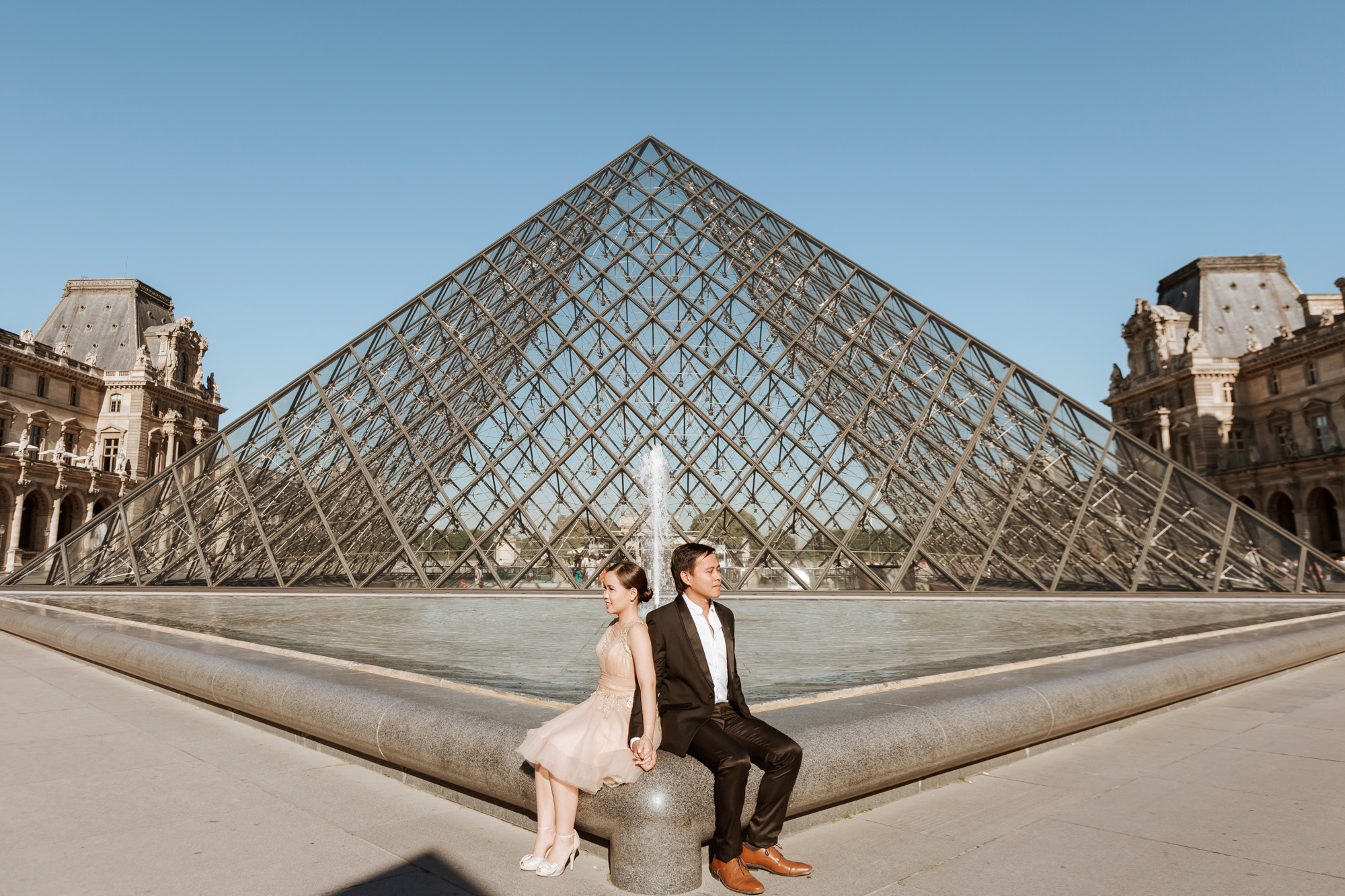 Pre-wedding couple portrait sitting by the Louvre Pyramid captured by Paris Photographer Federico Guendel