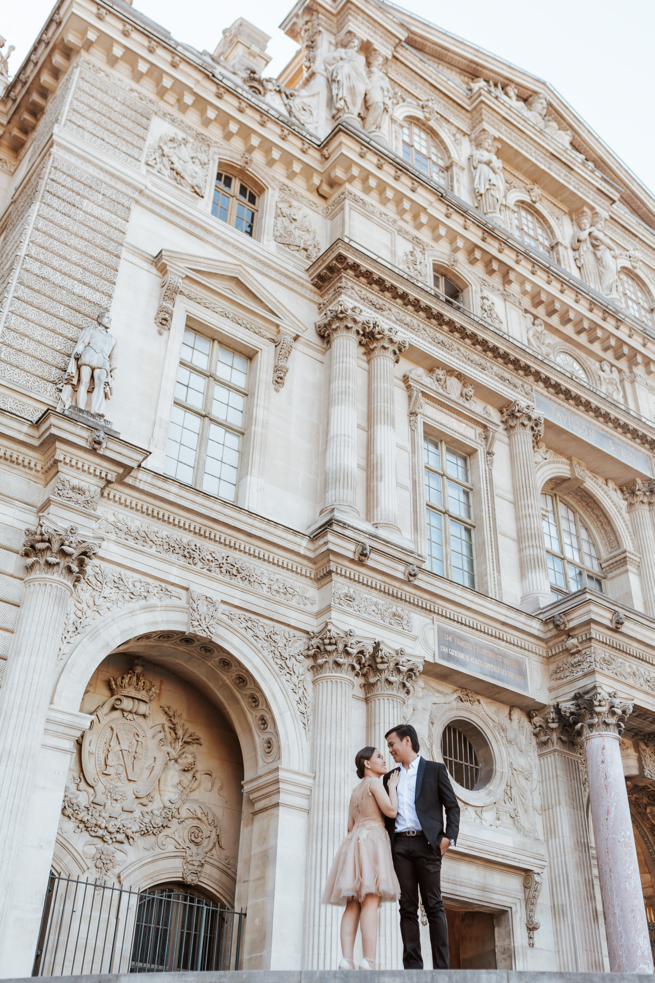 Pre-wedding couple portrait standing in the courtyard of the Louvre Museum captured by Paris Photographer Federico Guendel