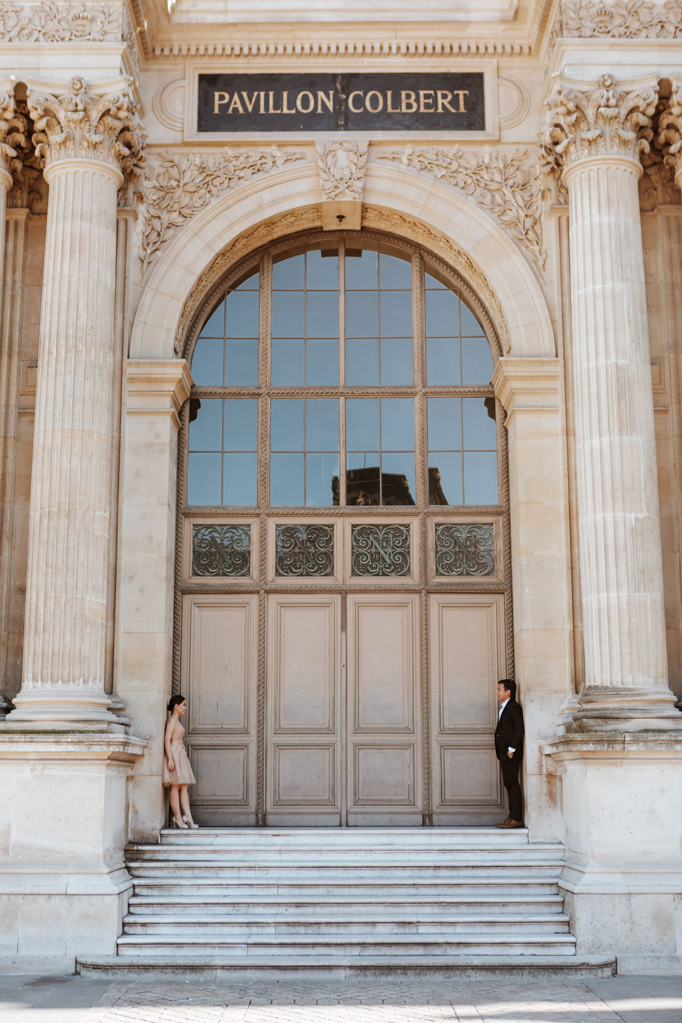 Pre-wedding couple portrait standing by Pavillon Colbert at the Louvre Museum captured by Paris Photographer Federico Guendel