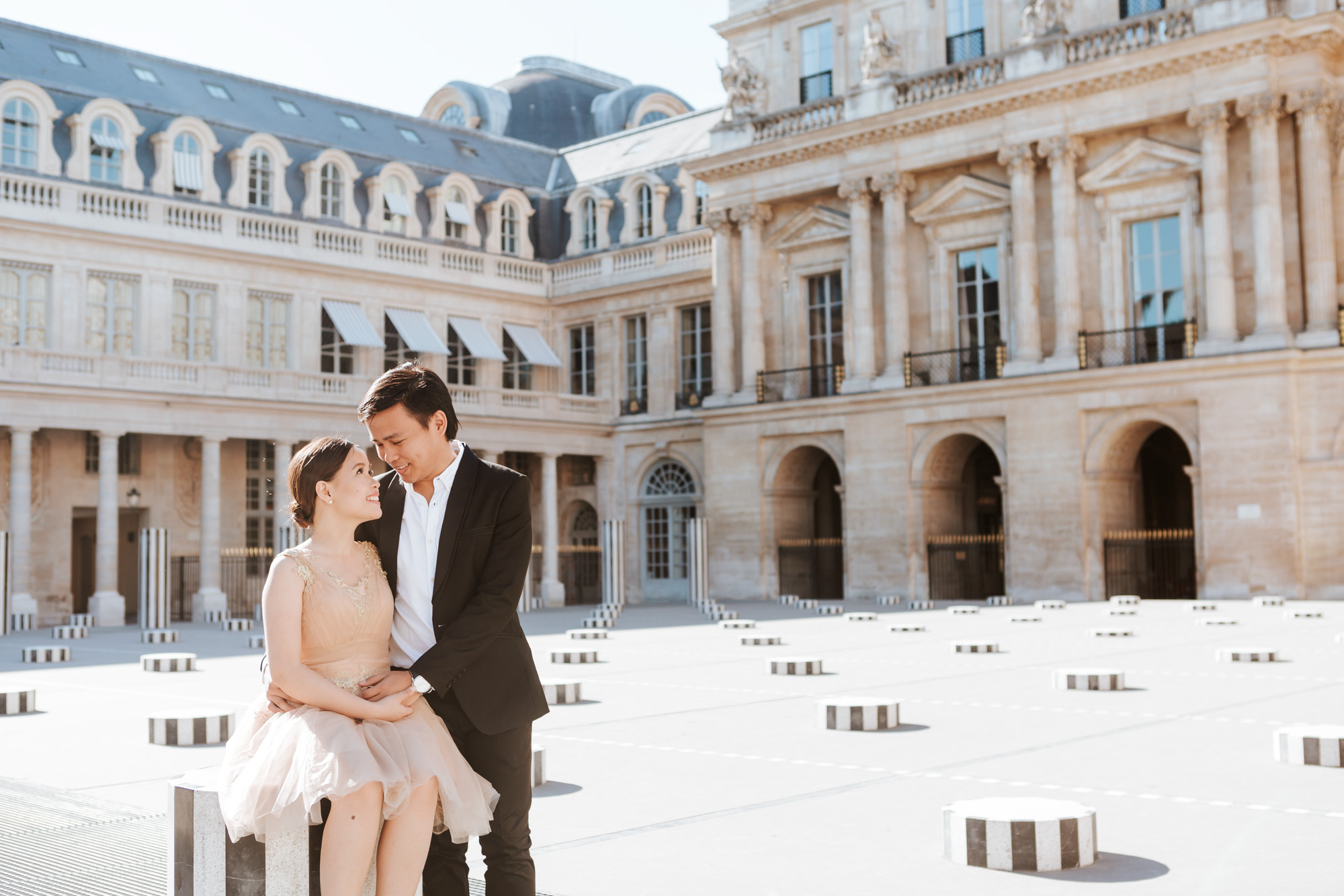Pre-wedding couple portrait sitting in the courtyard of Palais Royal captured by Paris Photographer Federico Guendel