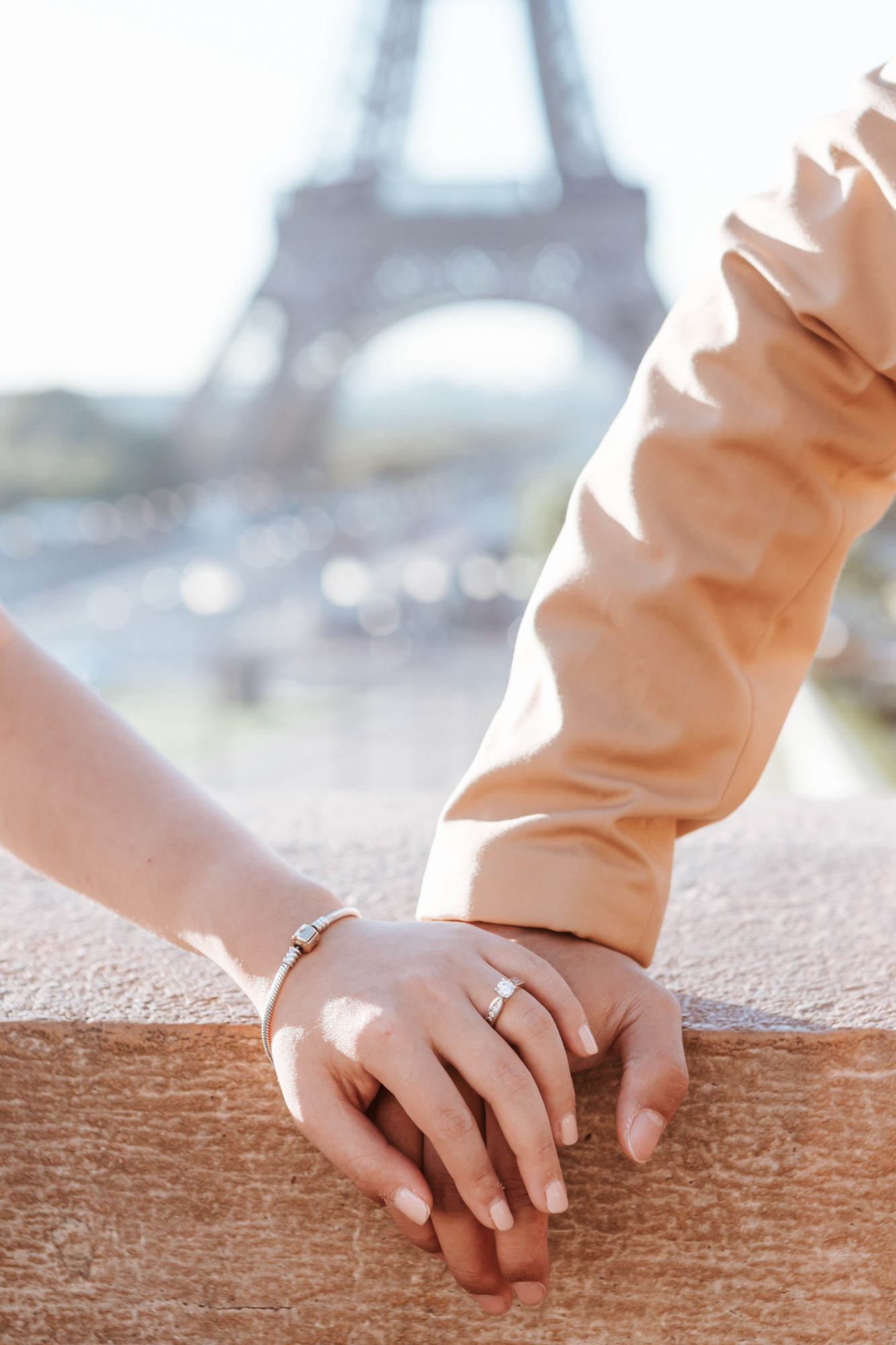 Pre-wedding couple holding hands with engagement ring by the Eiffel Tower in sunrise captured by Photographer in Paris Federico Guendel