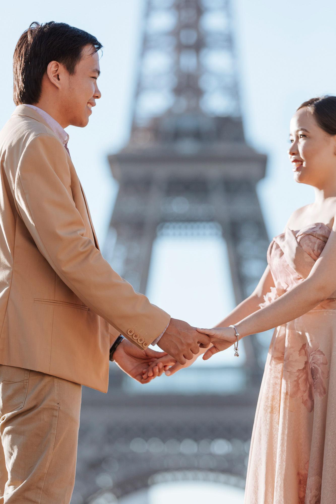 Pre-wedding couple portrait holding hands and smiling by the Eiffel Tower in sunrise captured by Photographer in Paris Federico Guendel