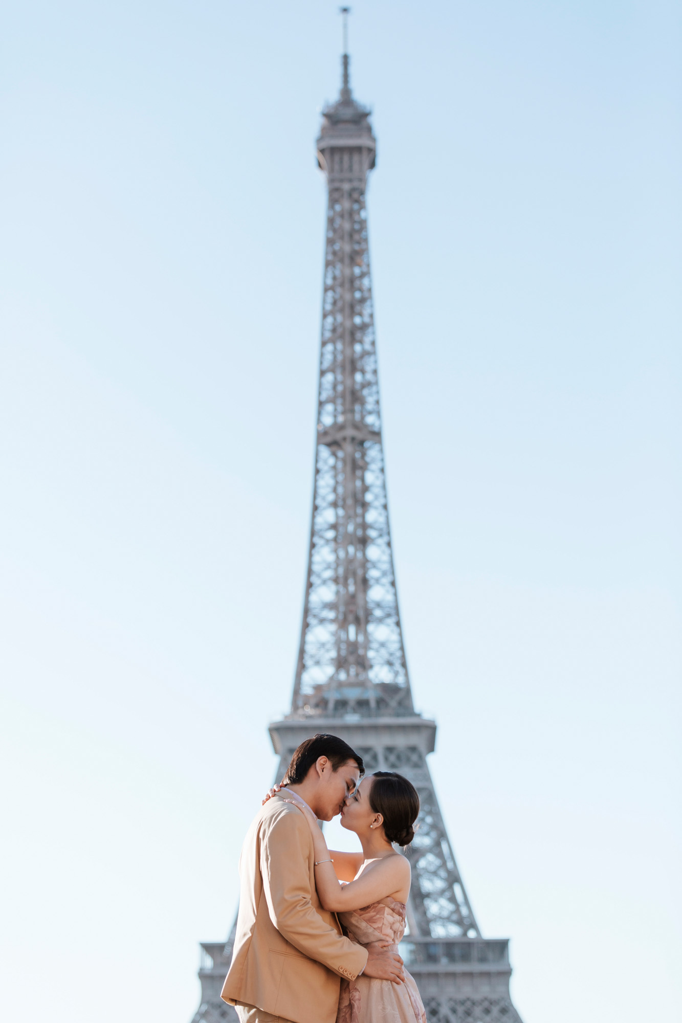 Pre-wedding romantic couple portrait session kissing by the Eiffel Tower in sunrise captured by Photographer in Paris Federico Guendel