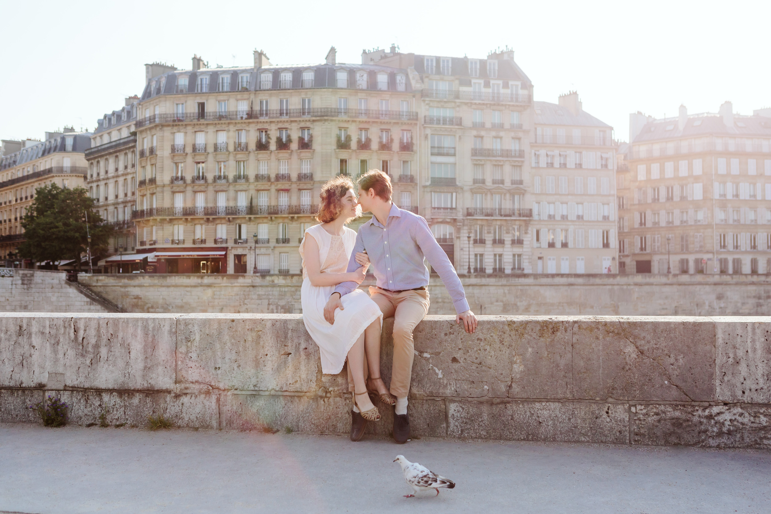 Couple in love kissing by Ile Saint Louis in Paris at sunrise with pigeon walking in the foreground captured by Paris Photographer Federico Guendel IheartParisFr