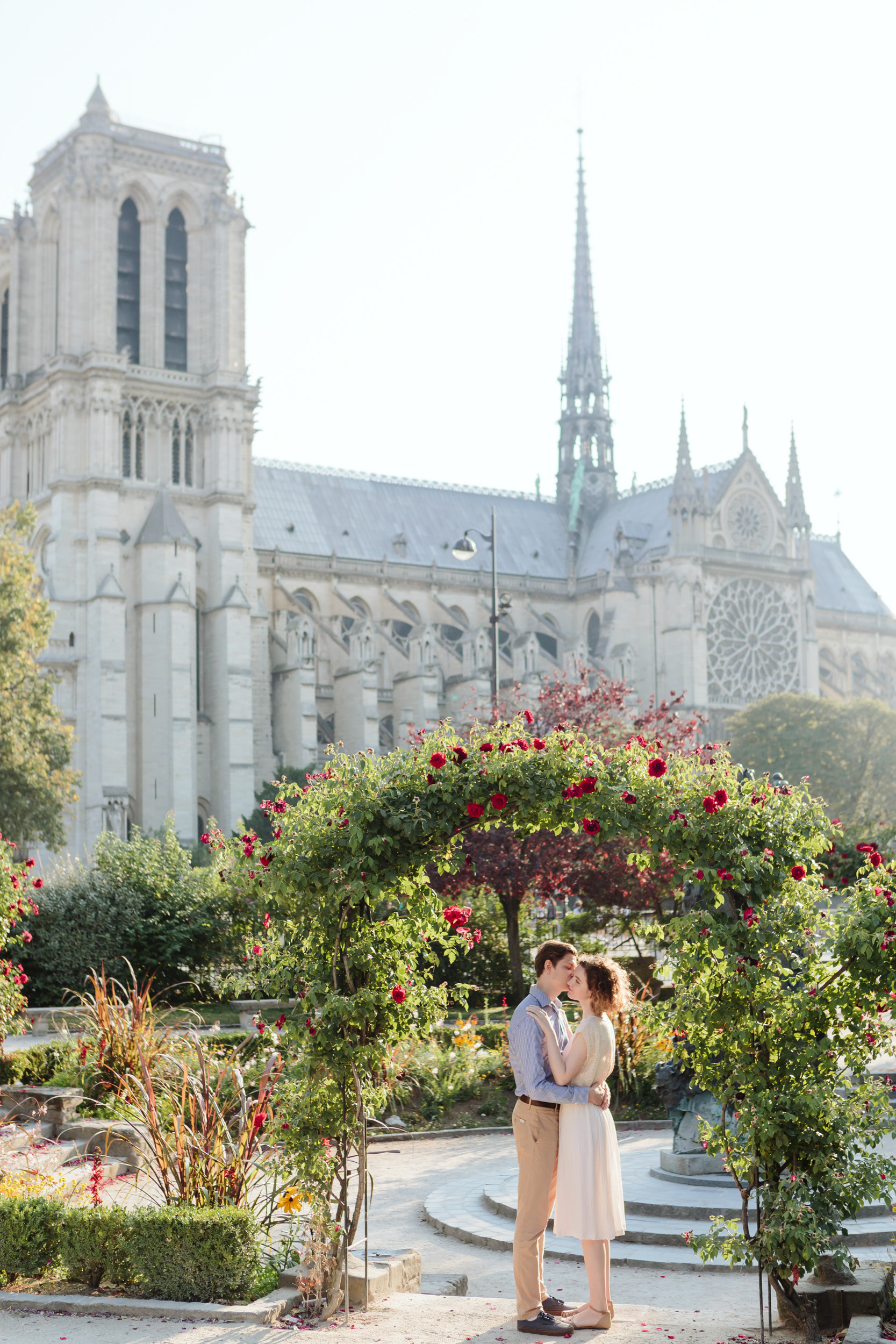 Couple in love kissing by Notre Dame Cathedral rose garden in Paris captured by Paris Photographer Federico Guendel IheartParisFr