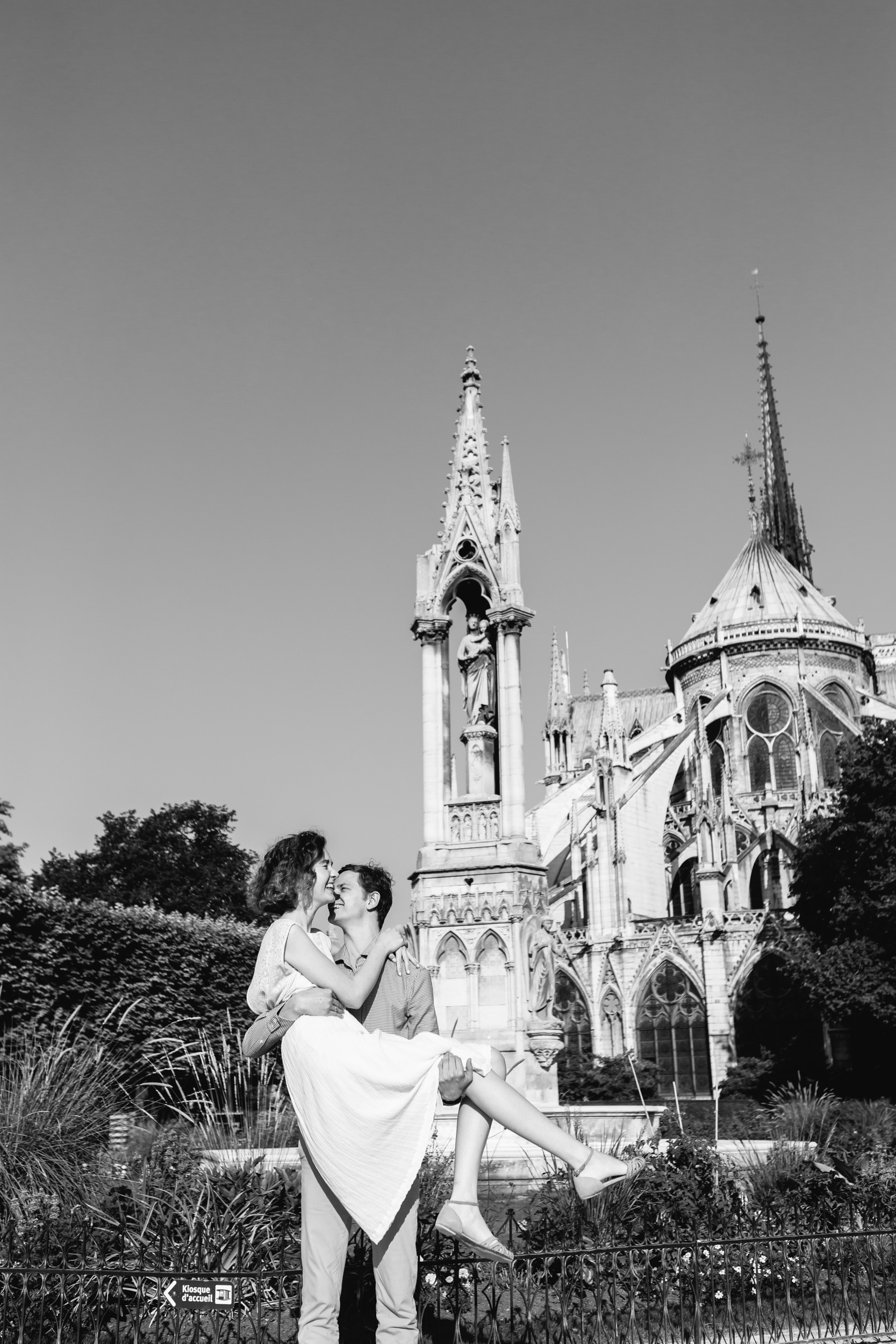 Man holding his wife in his arms by Notre Dame Cathedral garden in Paris - black and white photo captured by Paris Photographer Federico Guendel IheartParisFr