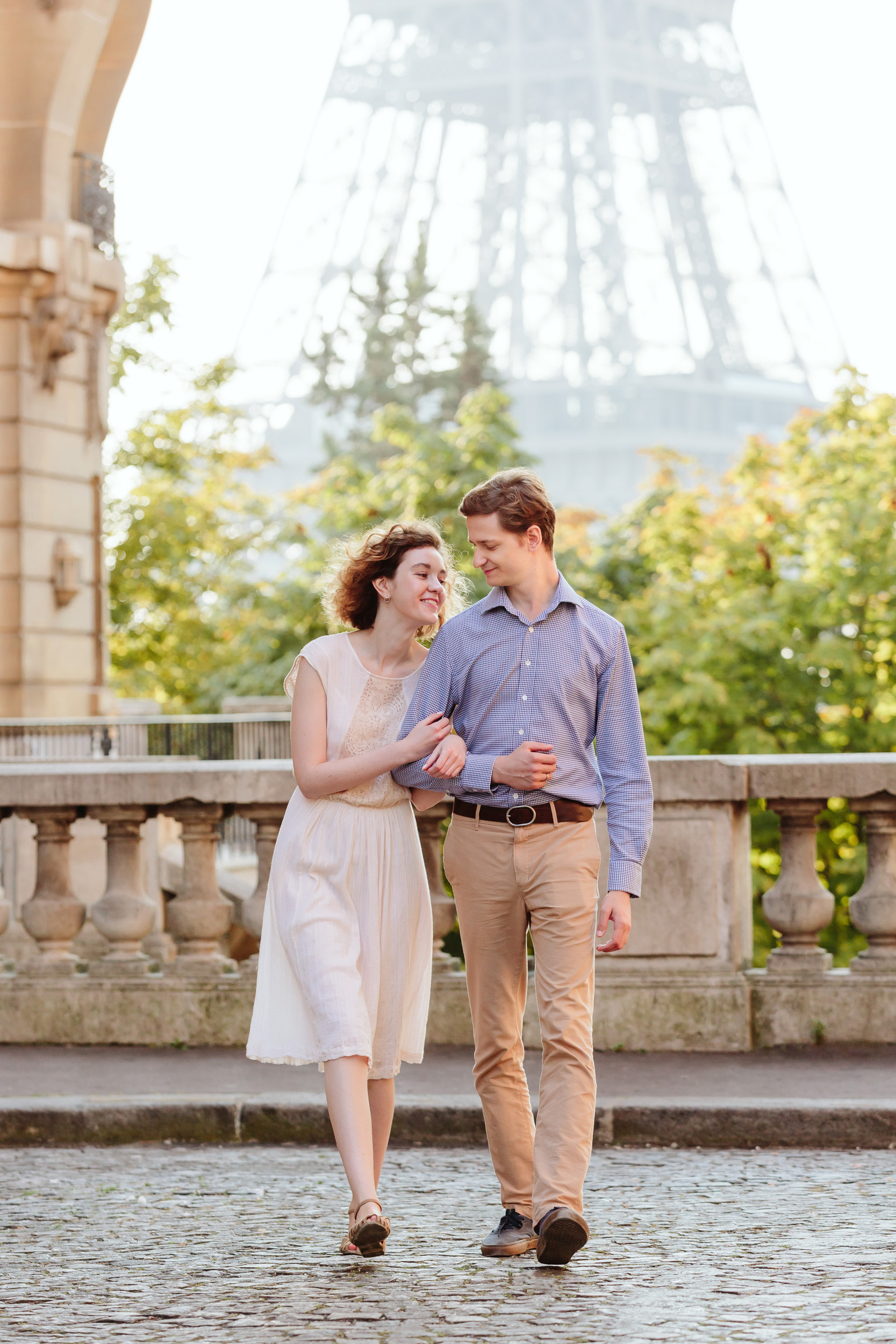 Travel love story couple walking next to Eiffel Tower at Passy captured by Paris Photographer Federico Guendel IheartParisFr