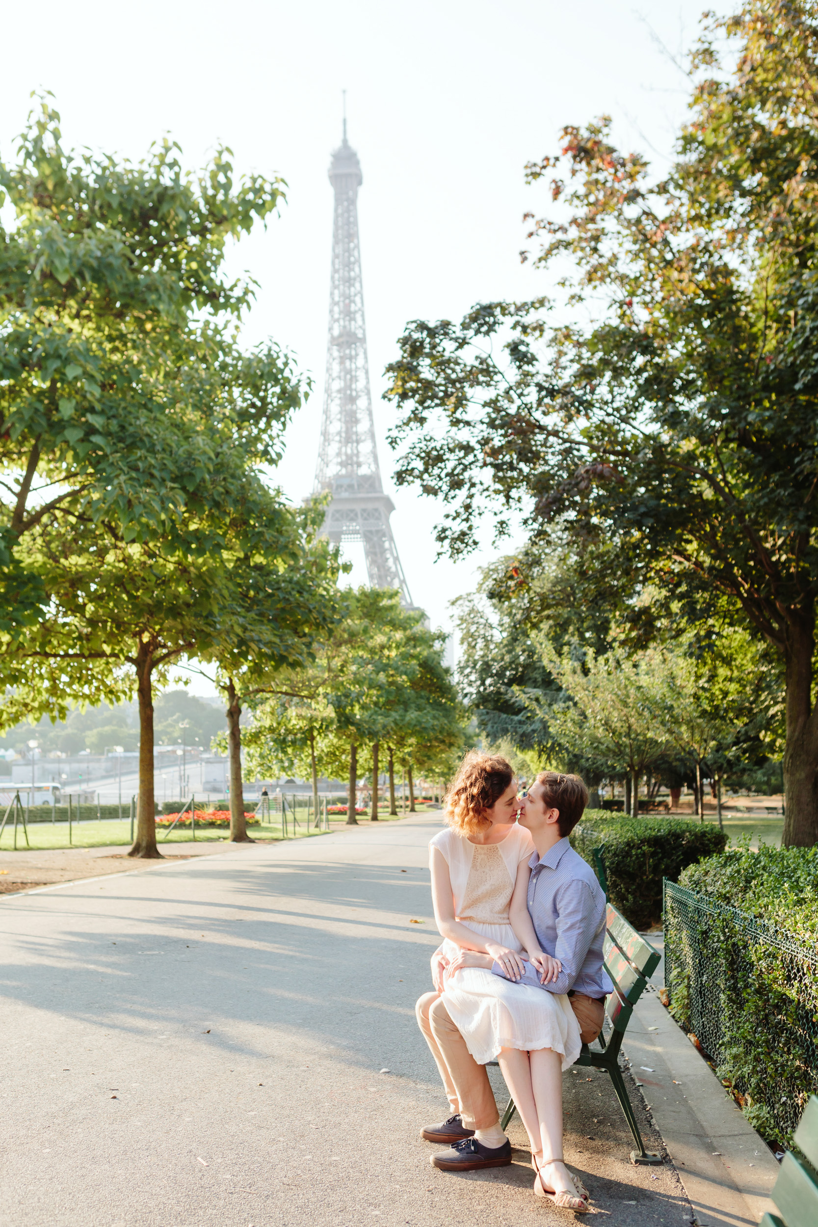 Couple sitting on a bench and kissing at Trocadero by the Eiffel Tower at sunrise captured by Paris Photographer Federico Guendel IheartParisFr