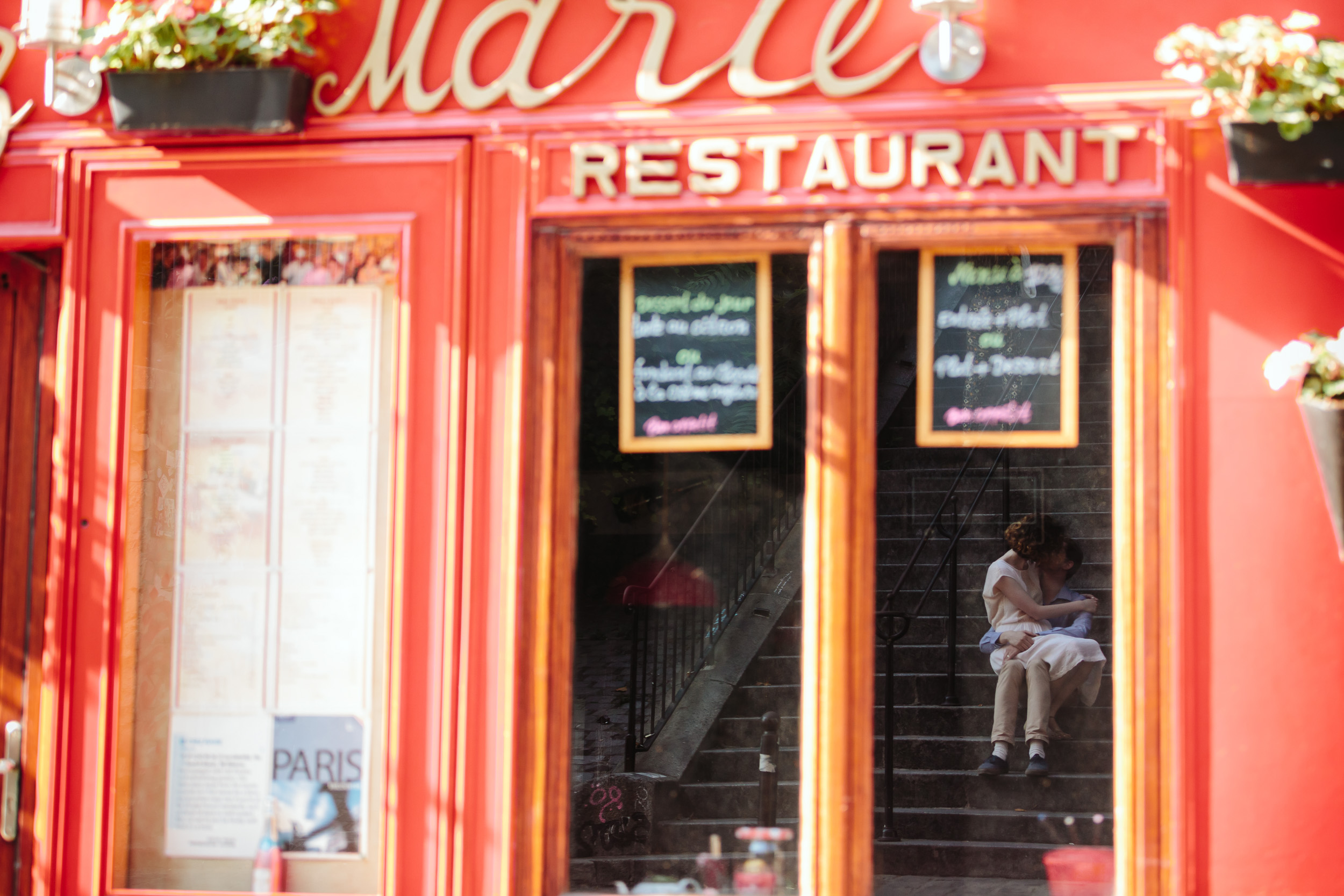Window reflection at Marie restaurant of a couple sitting on the steps in Montmartre captured by Paris Photographer Federico Guendel IheartParisFr