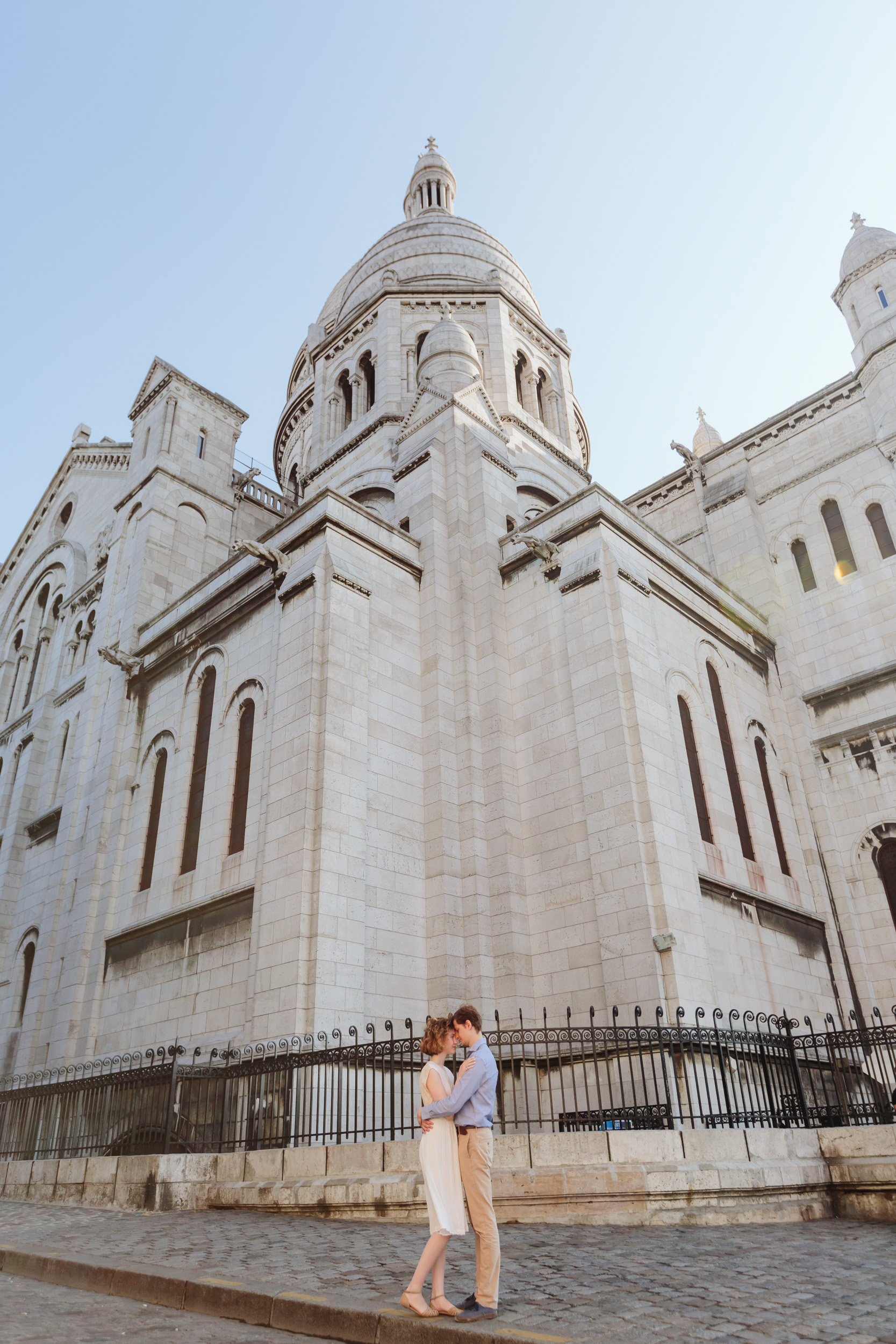 Couple in love standing by Sacre Coeur Cathedral at Montmartre captured by Paris Photographer Federico Guendel IheartParisFr