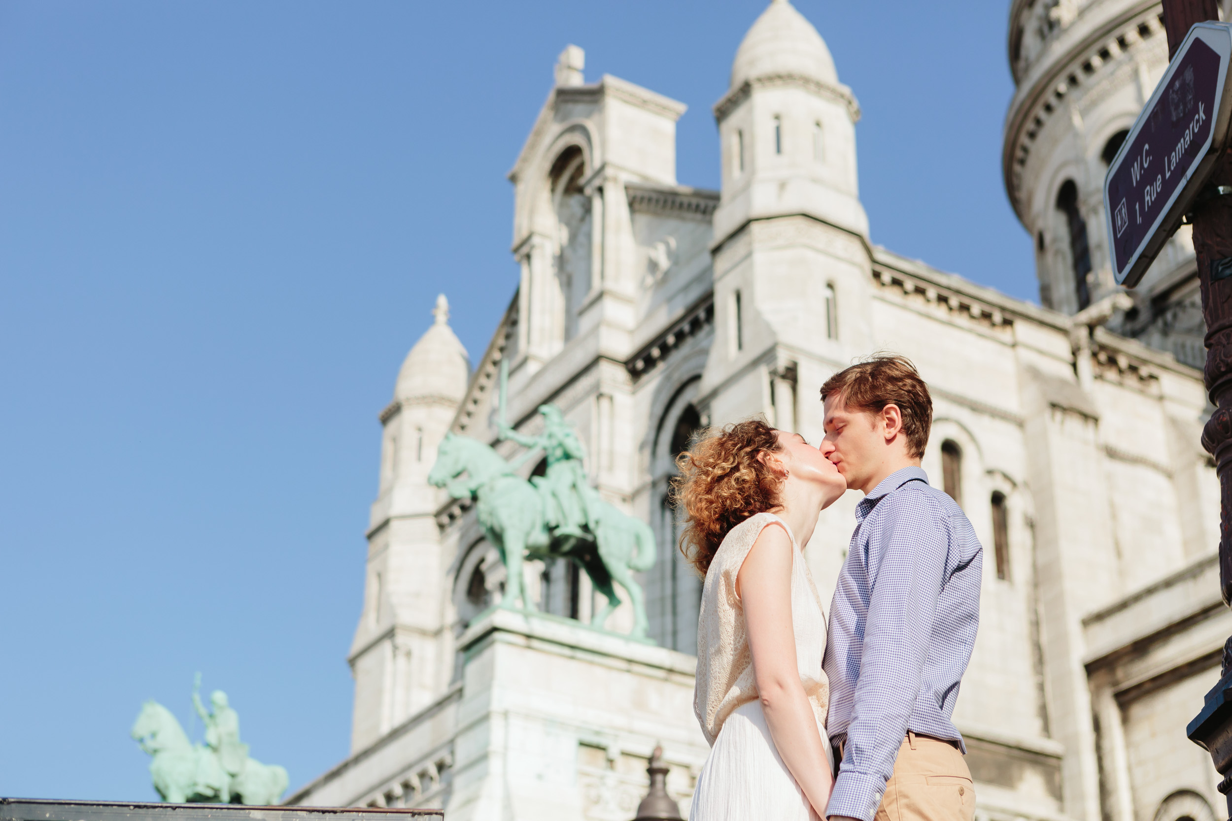 Paris Travel Love Story couple kissing by Sacre Coeur Cathedral at Montmartre captured by Paris Photographer Federico Guendel IheartParisFr