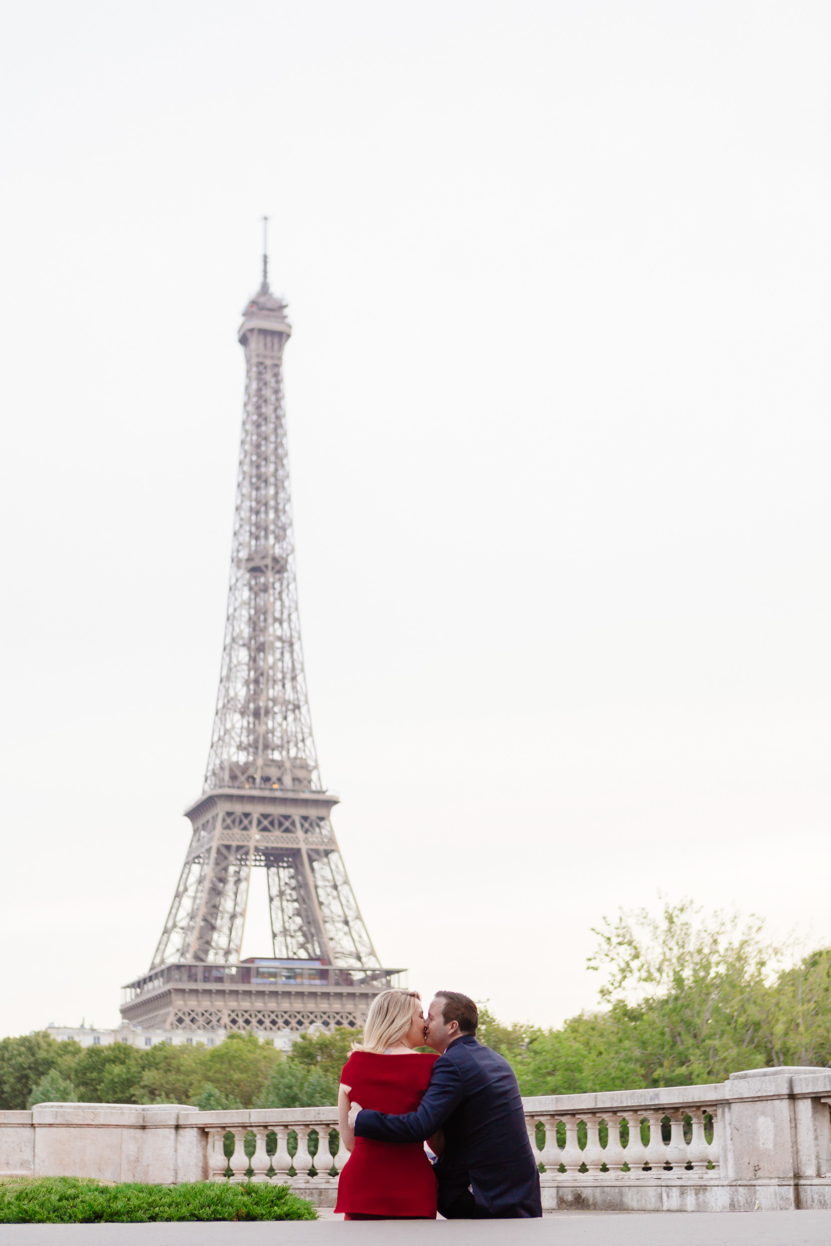 Romantic portrait of a couple kissing at bridge Bir Hakeim with the view of the Eiffel Tower captured by Paris Photographer Federico Guendel www.iheartparis.fr