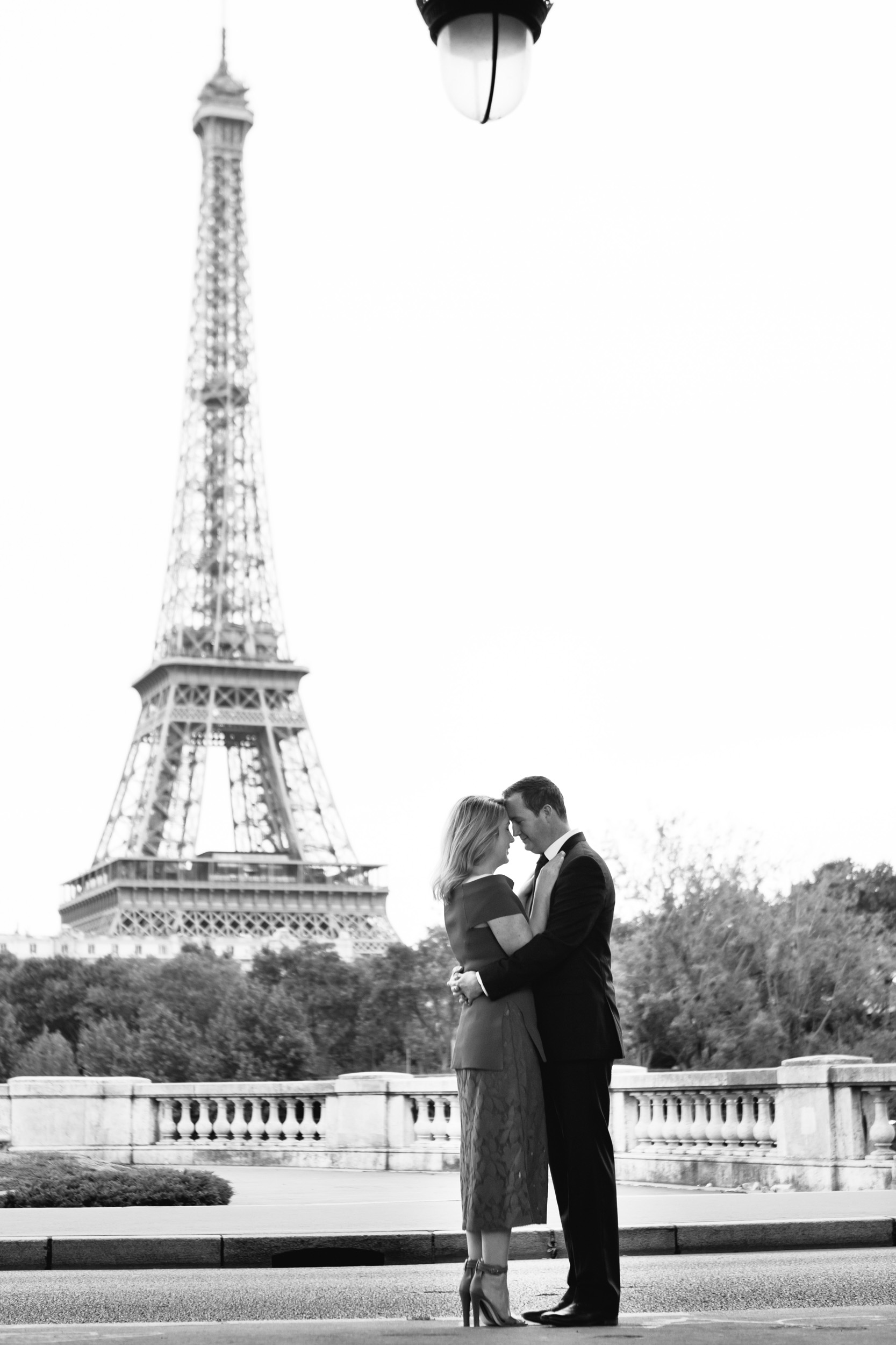 Romantic black and white portrait of a couple at bridge Bir Hakeim with the view of the Eiffel Tower captured by Paris Photographer Federico Guendel www.iheartparis.fr