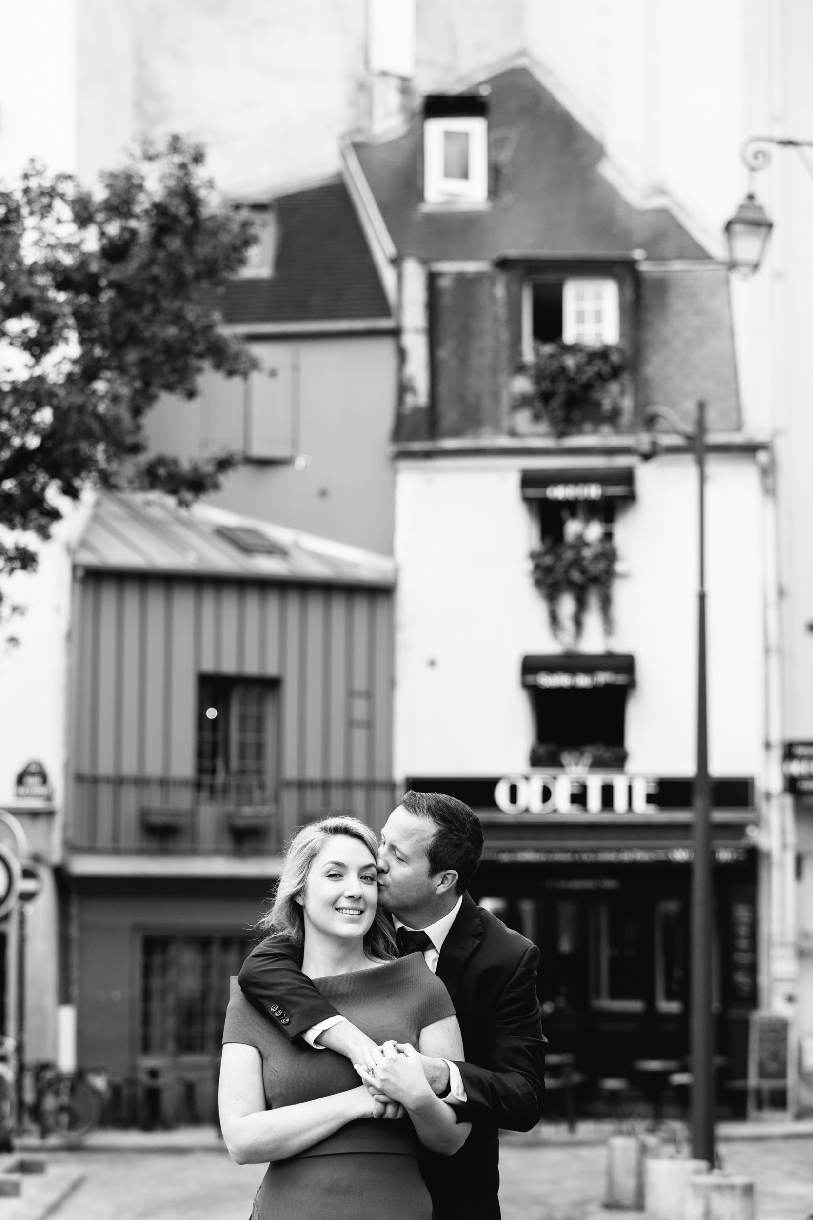 Romantic black and white portrait of a couple hugging in front of cafe Odette in Saint Germain captured by Paris Photographer Federico Guendel www.iheartparis.fr