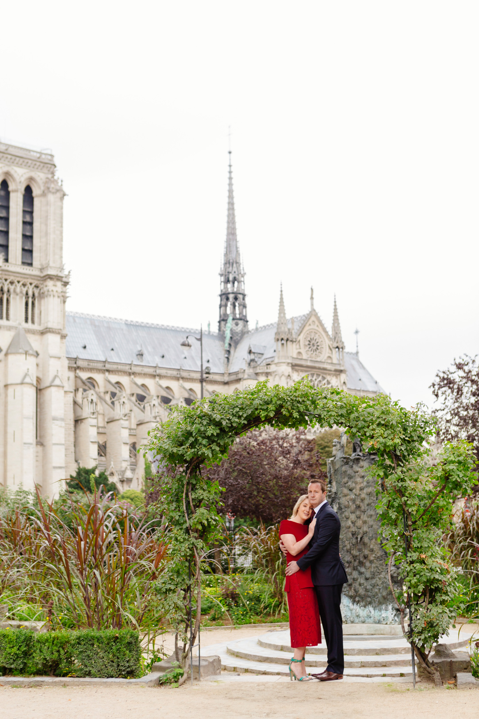 Romantic portrait of a couple hugging with the view of Notre Dame Cathedral captured by Paris Photographer Federico Guendel www.iheartparis.fr