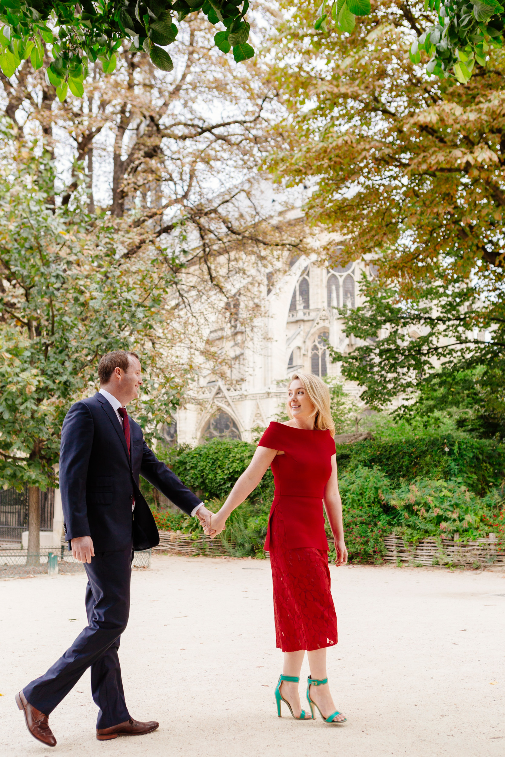Romantic portrait of a couple holding hands with the view of Notre Dame Cathedral captured by Paris Photographer Federico Guendel www.iheartparis.fr