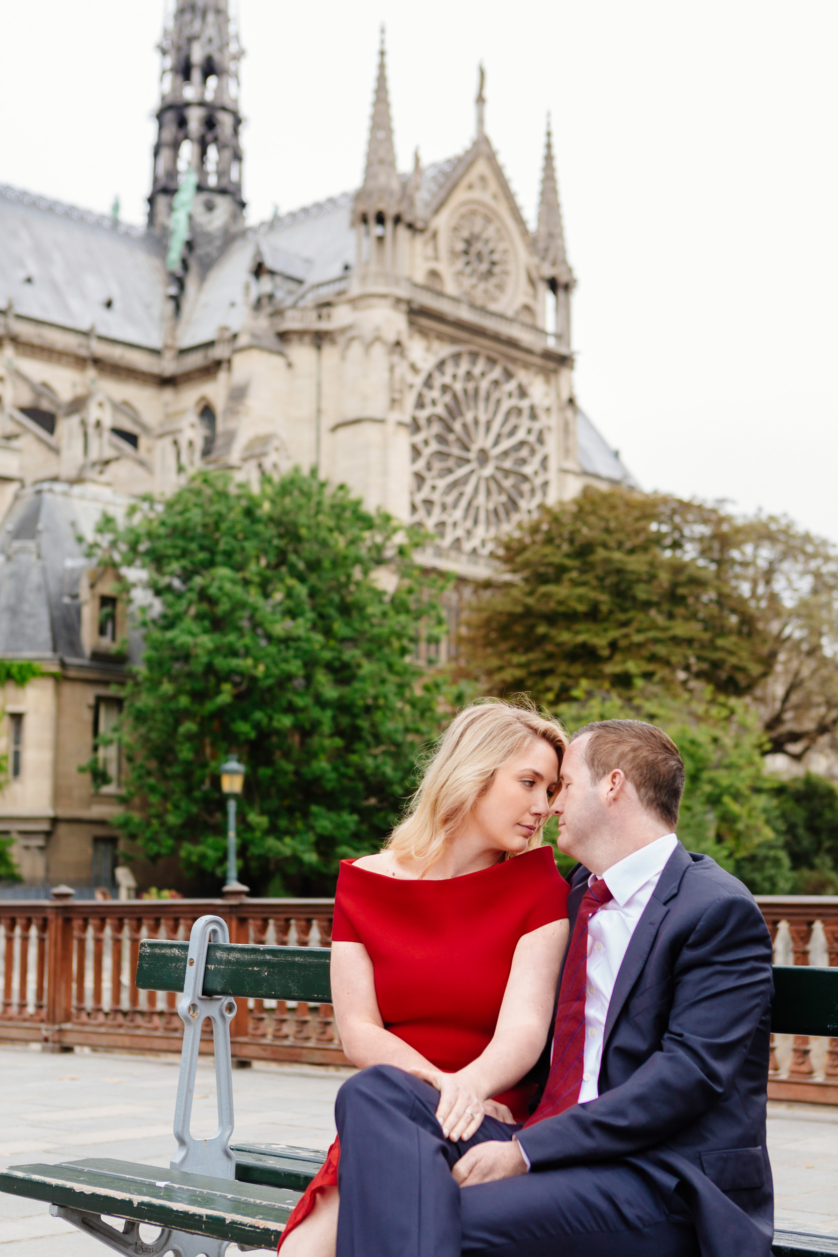 Romantic portrait of a couple sitting on a bench with the view of Notre Dame Cathedral captured by Paris Photographer Federico Guendel www.iheartparis.fr