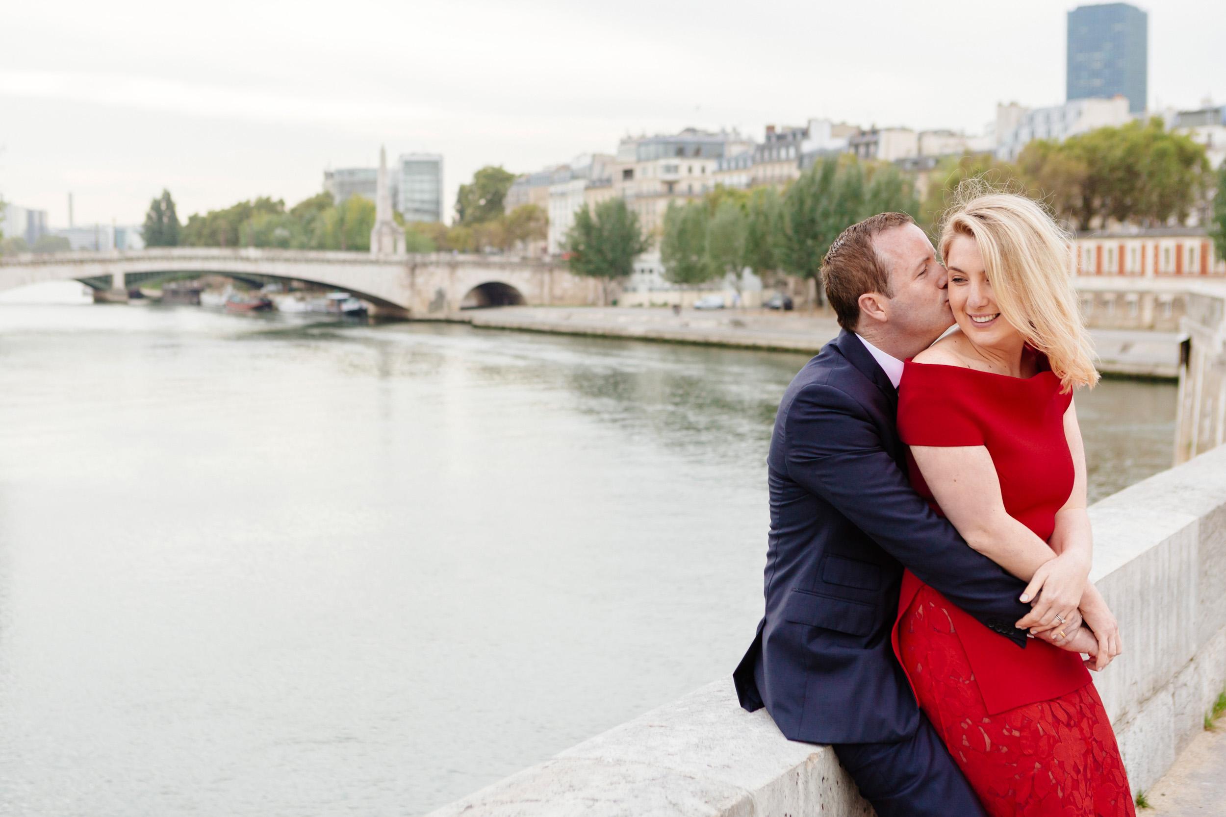 Romantic portrait of a couple hugging at Ile de la Cite with the view of Seine river captured by Paris Photographer Federico Guendel www.iheartparis.fr