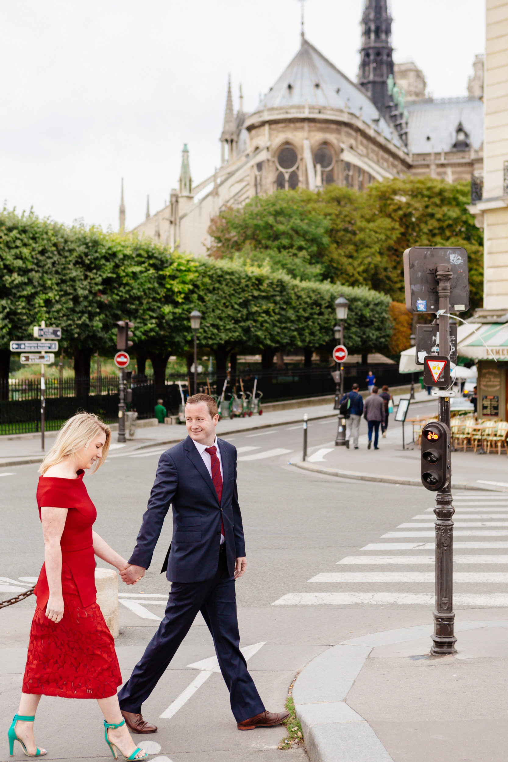 Romantic portrait of a couple holding hands and crossing the road with the view of Notre Dame Cathedral captured by Paris Photographer Federico Guendel www.iheartparis.fr