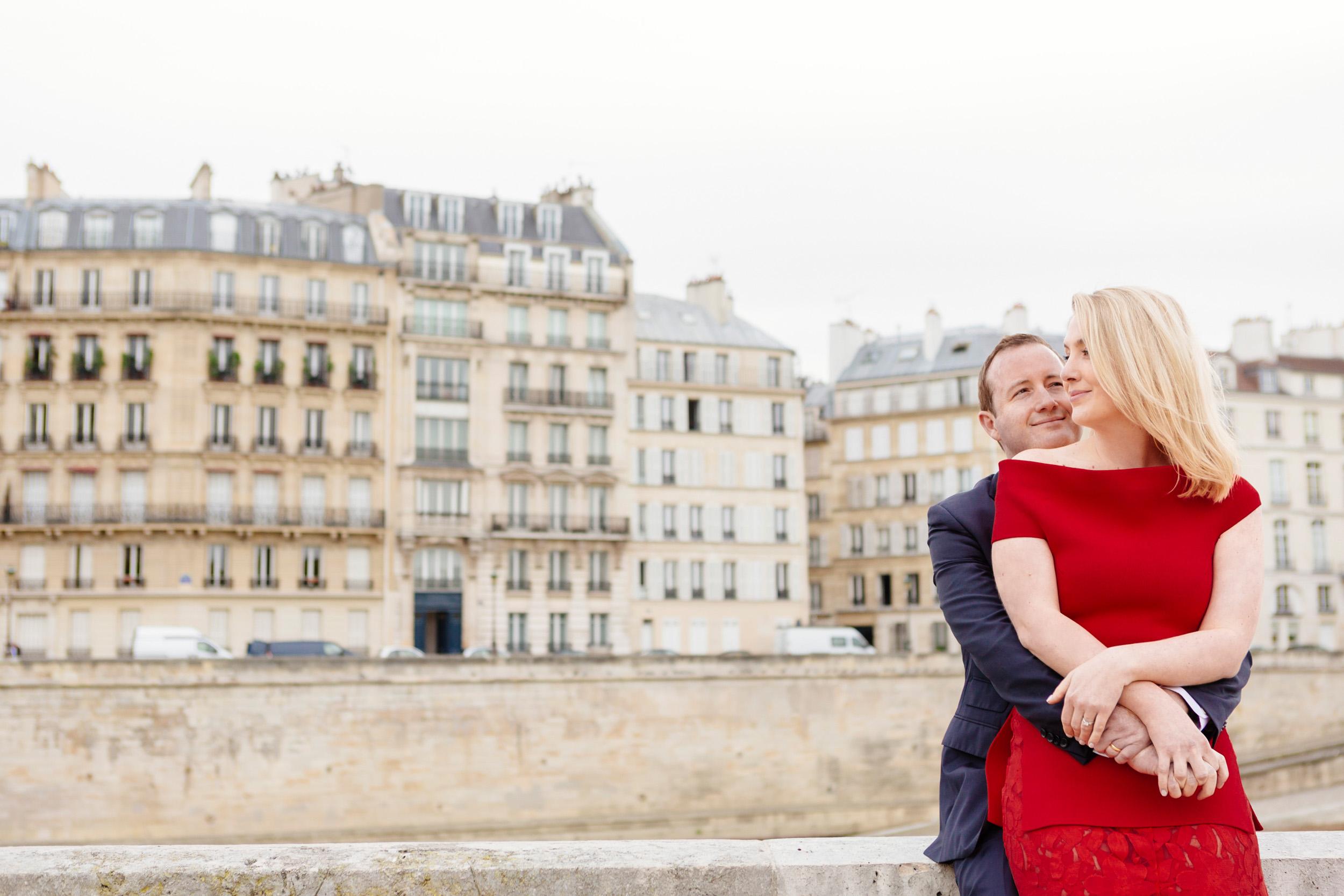 Romantic portrait of a couple hugging at Ile de la Cite with the view of Ile Saint Louis captured by Paris Photographer Federico Guendel www.iheartparis.fr