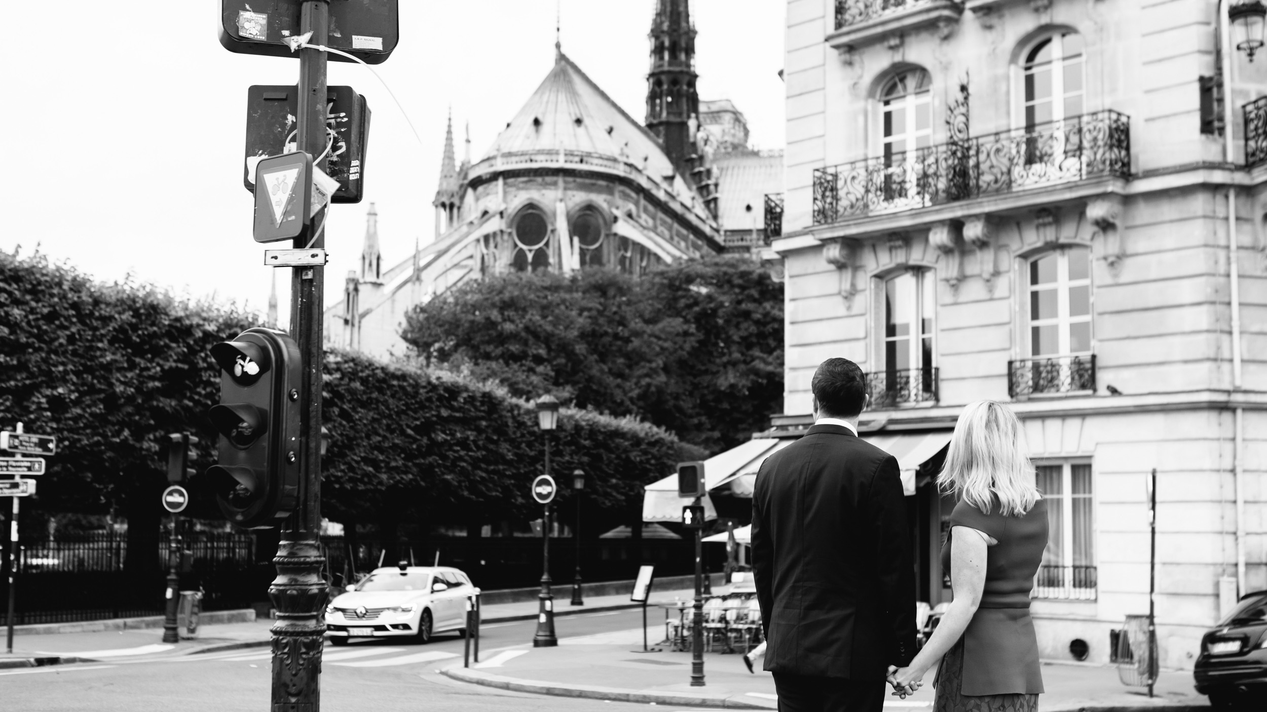 Romantic black and white portrait of a couple holding hands with the view of Notre Dame Cathedral captured by Paris Photographer Federico Guendel www.iheartparis.fr