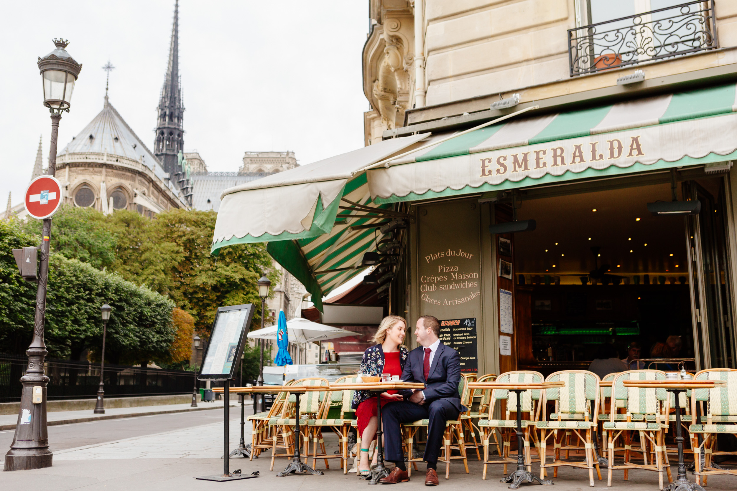 Couple sharing a croissant and coffee at cafe Esmeralda with the view of Notre Dame Cathedral captured by Paris Photographer Federico Guendel www.iheartparis.fr