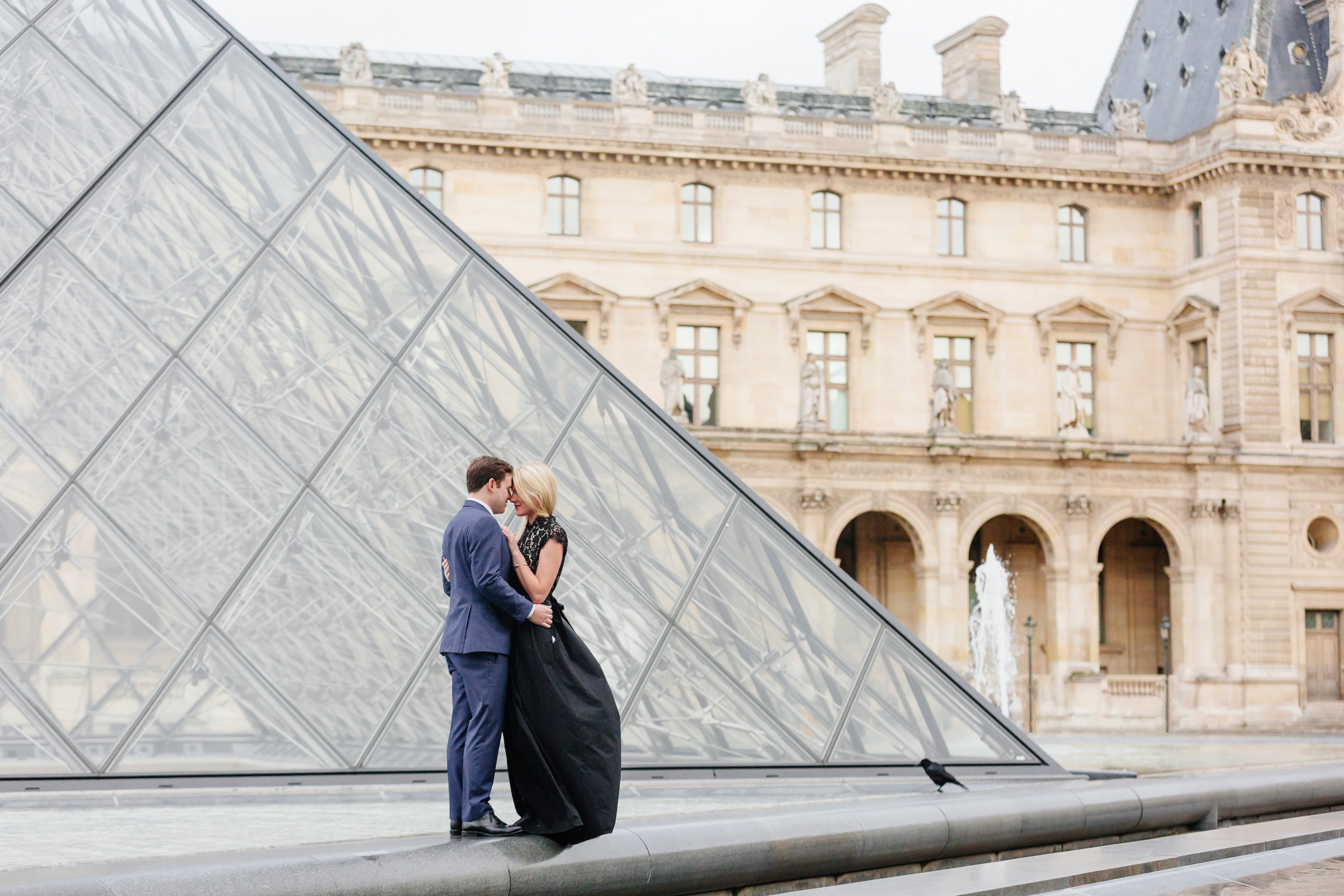 Paris vacation couple portrait hugging by Louvre Museum Pyramid captured by Paris Photographer Federico Guendel www.iheartparis.fr