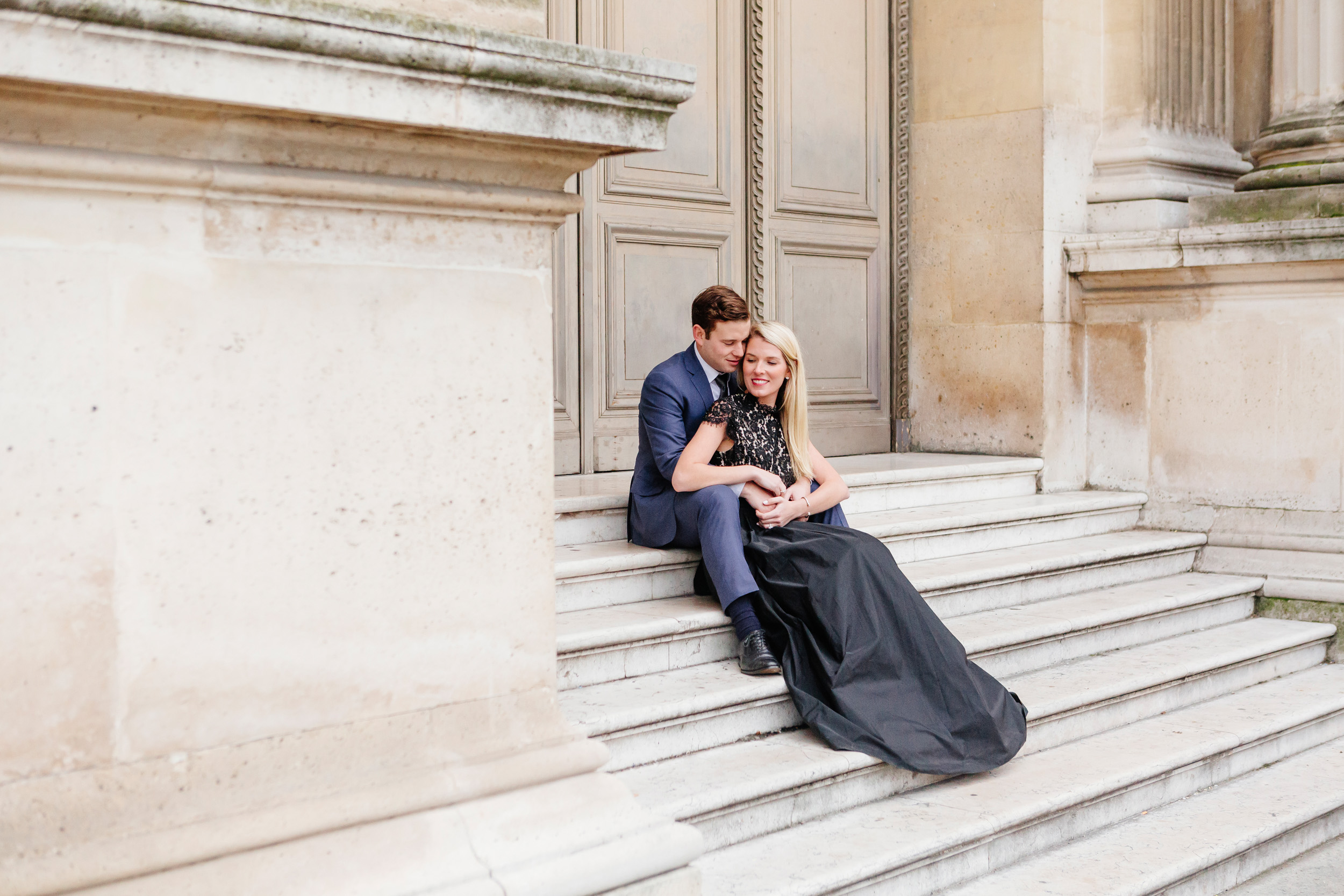 Paris vacation couple portrait sitting on the steps in the courtyard of Louvre Museum captured by Paris Photographer Federico Guendel www.iheartparis.fr