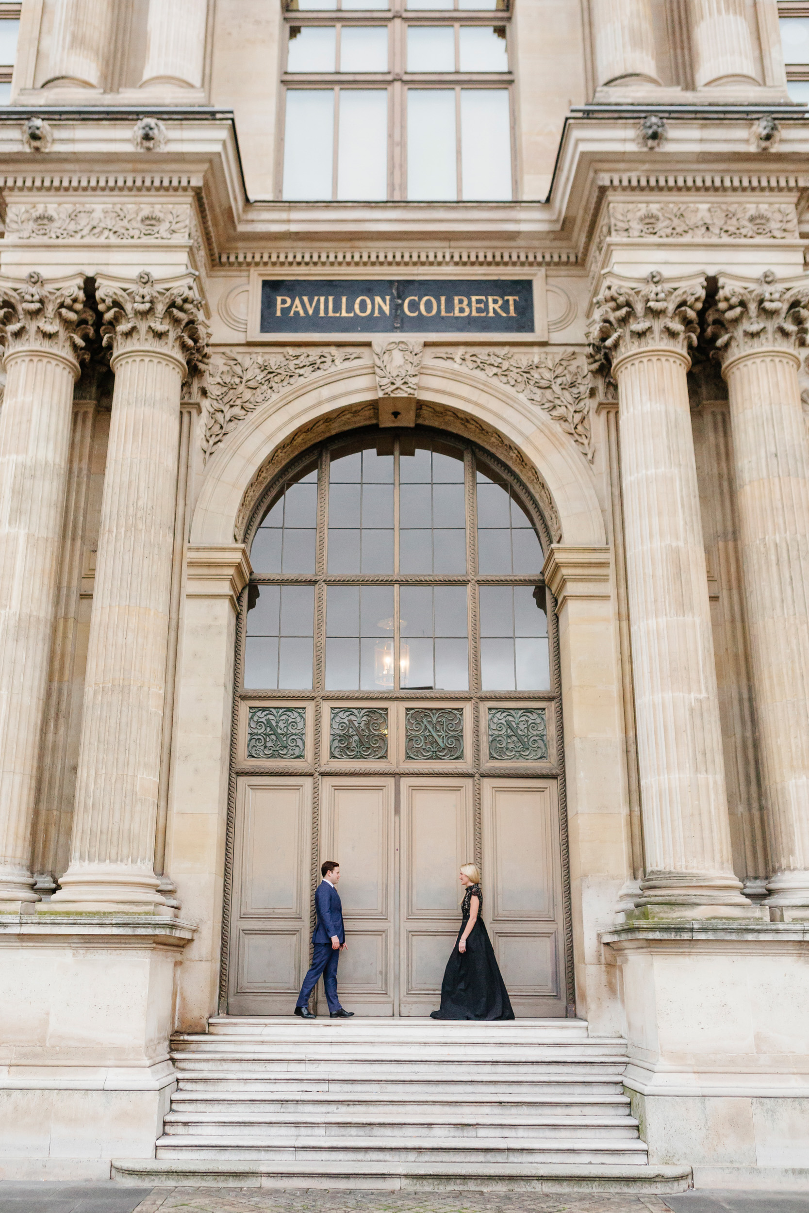 Paris vacation couple portrait standing by the door of Pavillon Colbert at Louvre Museum captured by Paris Photographer Federico Guendel www.iheartparis.fr