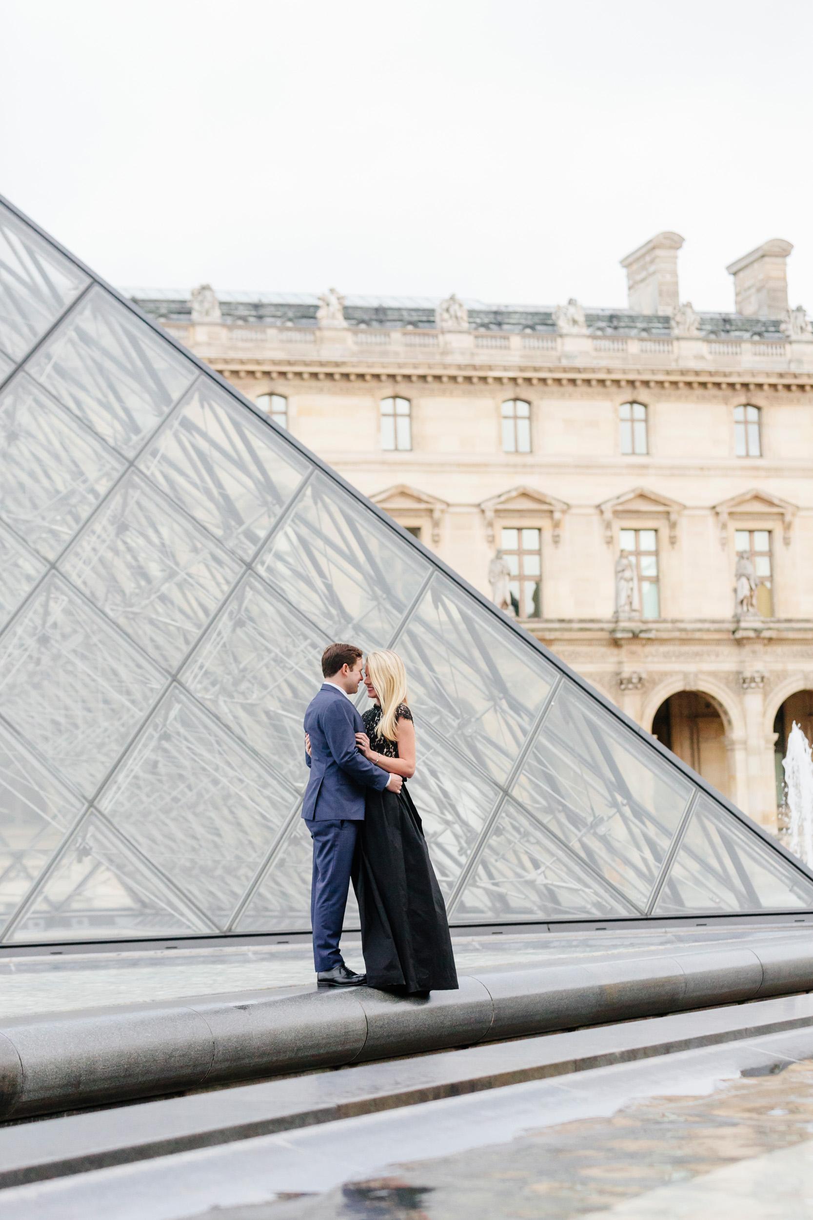 Paris vacation couple portrait standing by the Louvre Museum Pyramid captured by Paris Photographer Federico Guendel www.iheartparis.fr