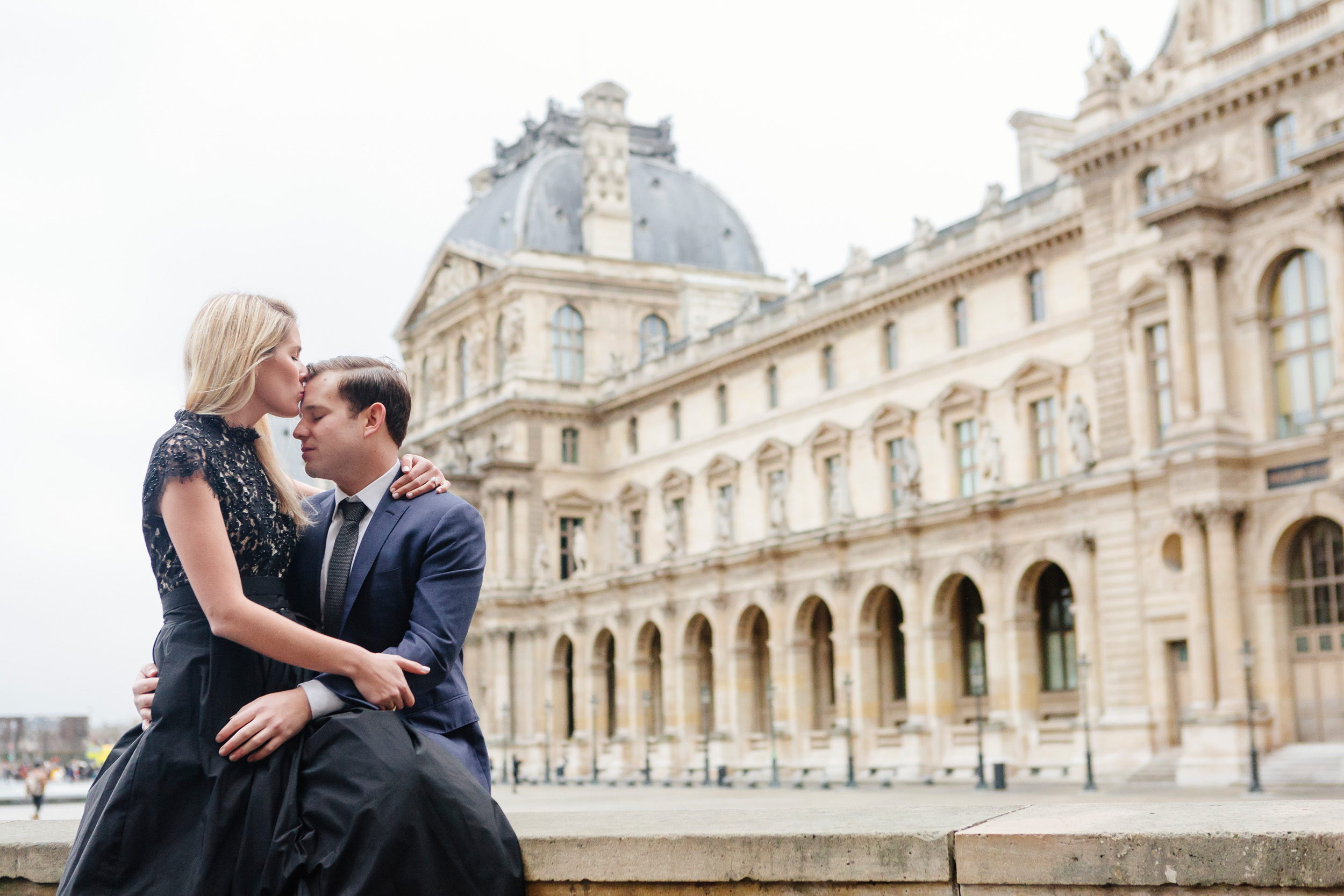 Paris vacation couple portrait kissing in the courtyard of Louvre Museum captured by Paris Photographer Federico Guendel www.iheartparis.fr