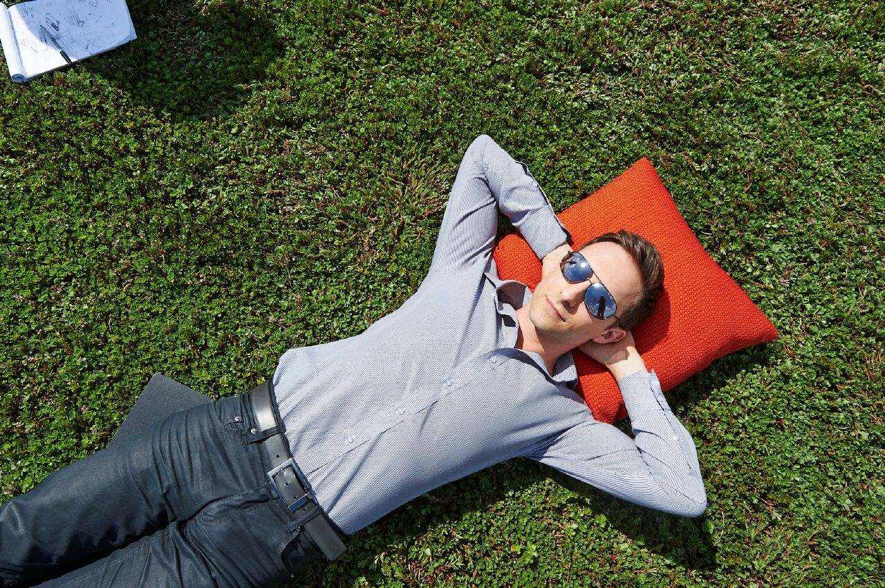 Designer  Nicolai Czumaj-Bront  lounges in the sun on top of Haworth headquarter's green roof in Holland, Michigan.