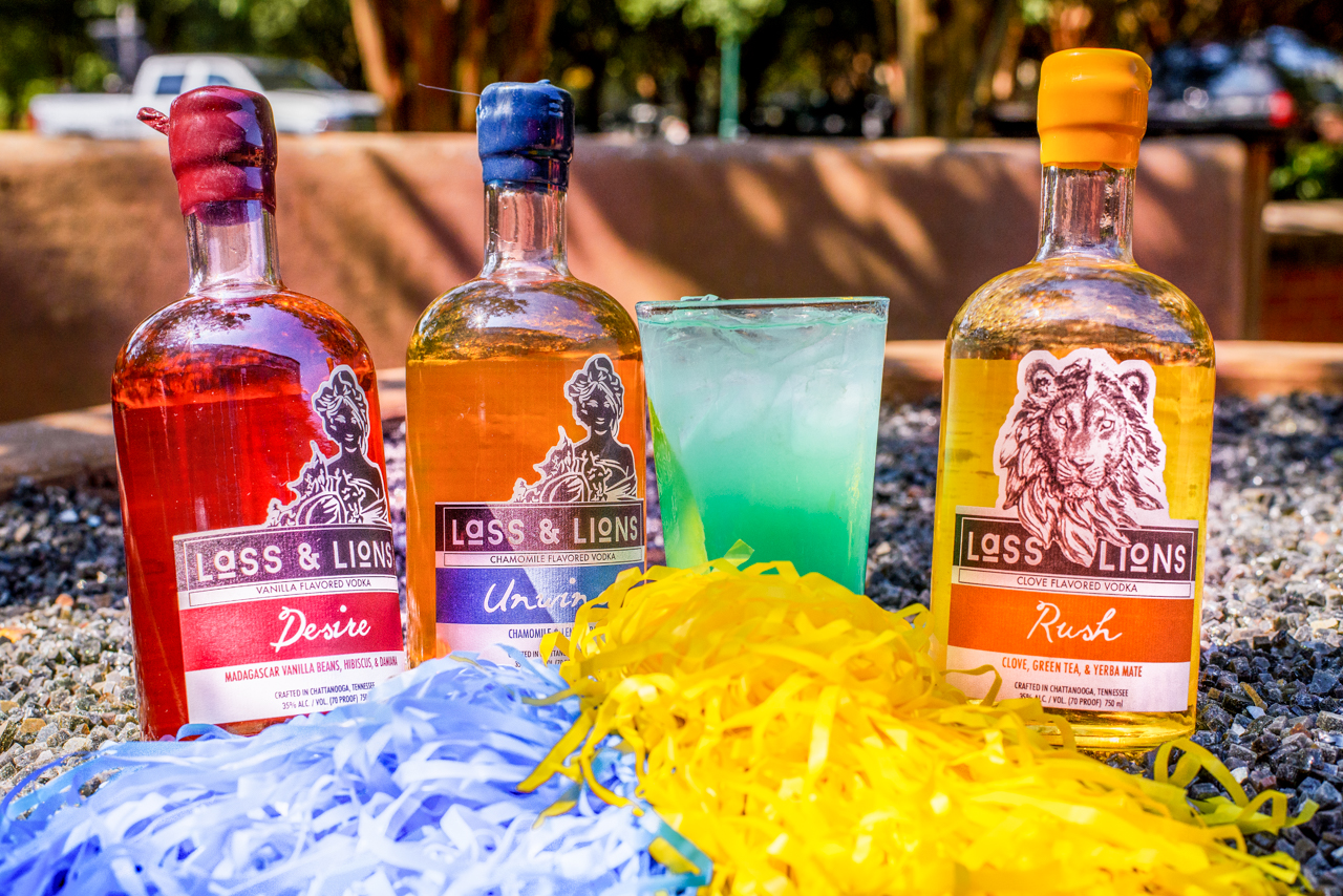 Blazing Blue & Gold - For all you Mocs fans!Ingredients:3/4 oz. Lass & Lions Desire Vodka3/4 oz. Lass & Lions Rush Vodka3/4 oz. Lass & Lions Unwind Vodka3/4 oz. Lass & Lass Craft Vodka (straight)4 oz. Sour MixTopped with Blue CuracaoCraft:Add all ingredients (besides the Blue Curacao) into a shaker, fill with ice and shake. Strain into pint glass, fill with ice and top with Blue Curacao. Go Mocs!