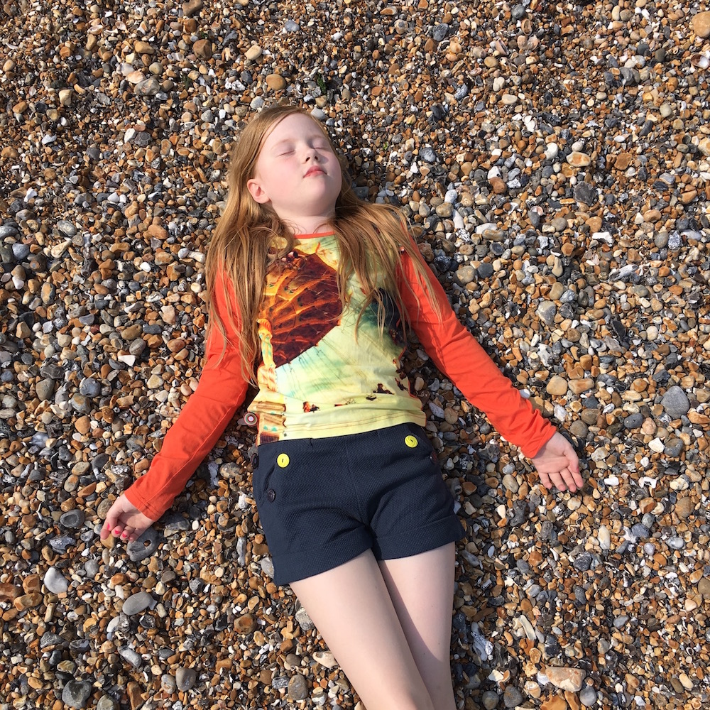 Girl wearing orange cardigan on beach