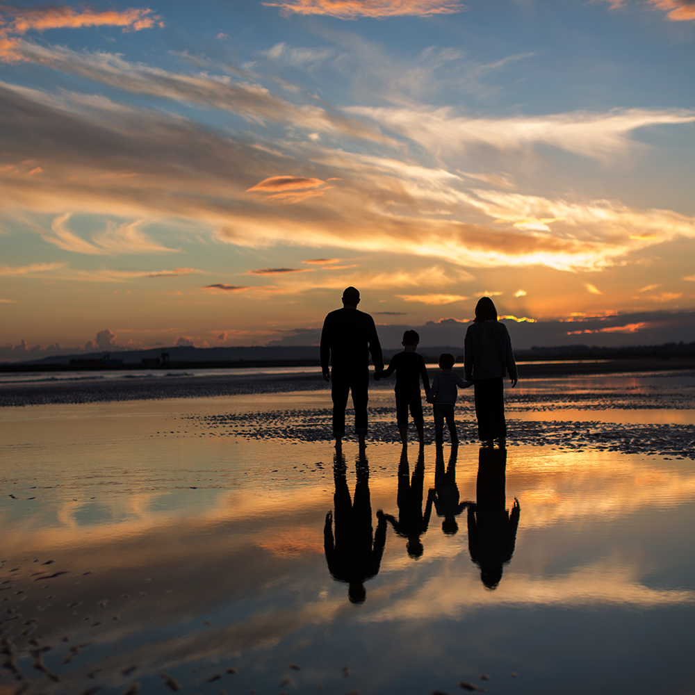 Family walking on beach as sunset