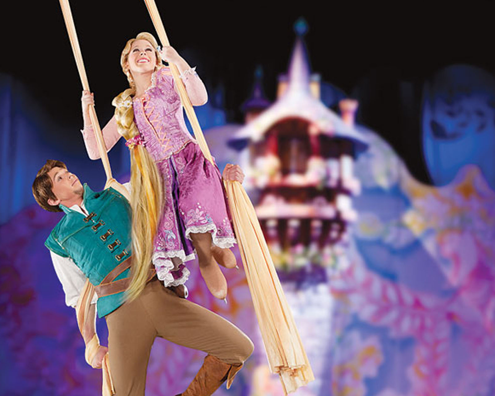 Rapunzel & Flynn hair silk fly over the ice with the Rapunzel's Tower in the background- Tower is attached to the side of the giant rotating set with two brightly painted curvilinear screens closed around the tower.