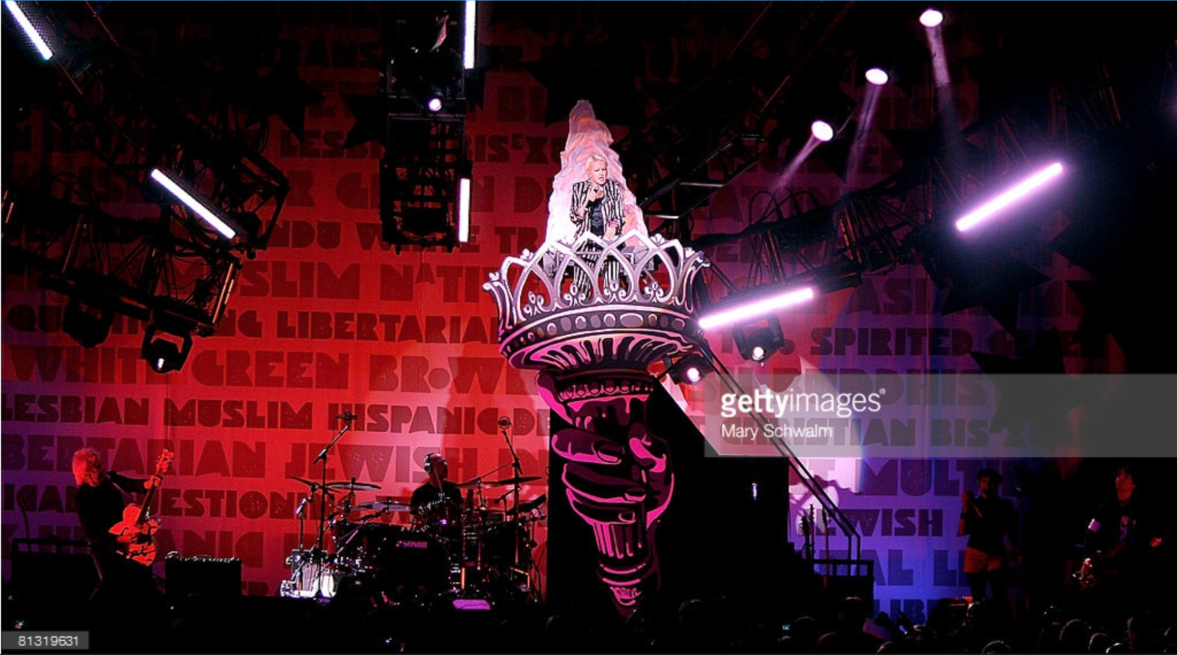 """Cyndi Lauper revealed on the Statue of Liberty Torch Wagon Unit.Surrounding the rest of the band is the """"Wall of Equality"""" backdrop."""