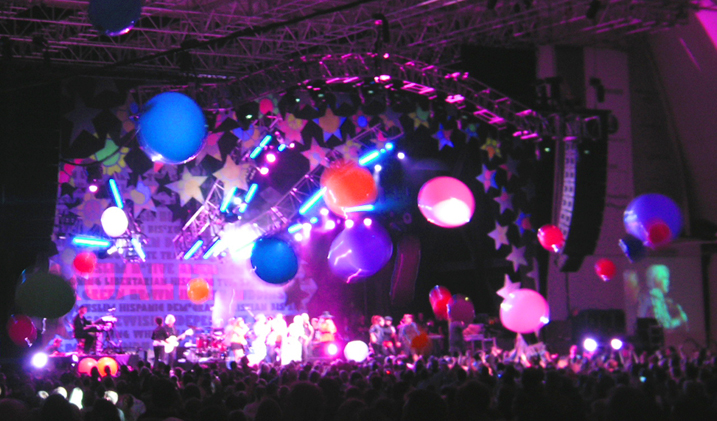 """True Colors Tour Finale.Big Balloons are tossed around and over the audience. The words """"Equality"""" come forward via invisible UV paint in the """"Wall of Equality"""" backdrop."""