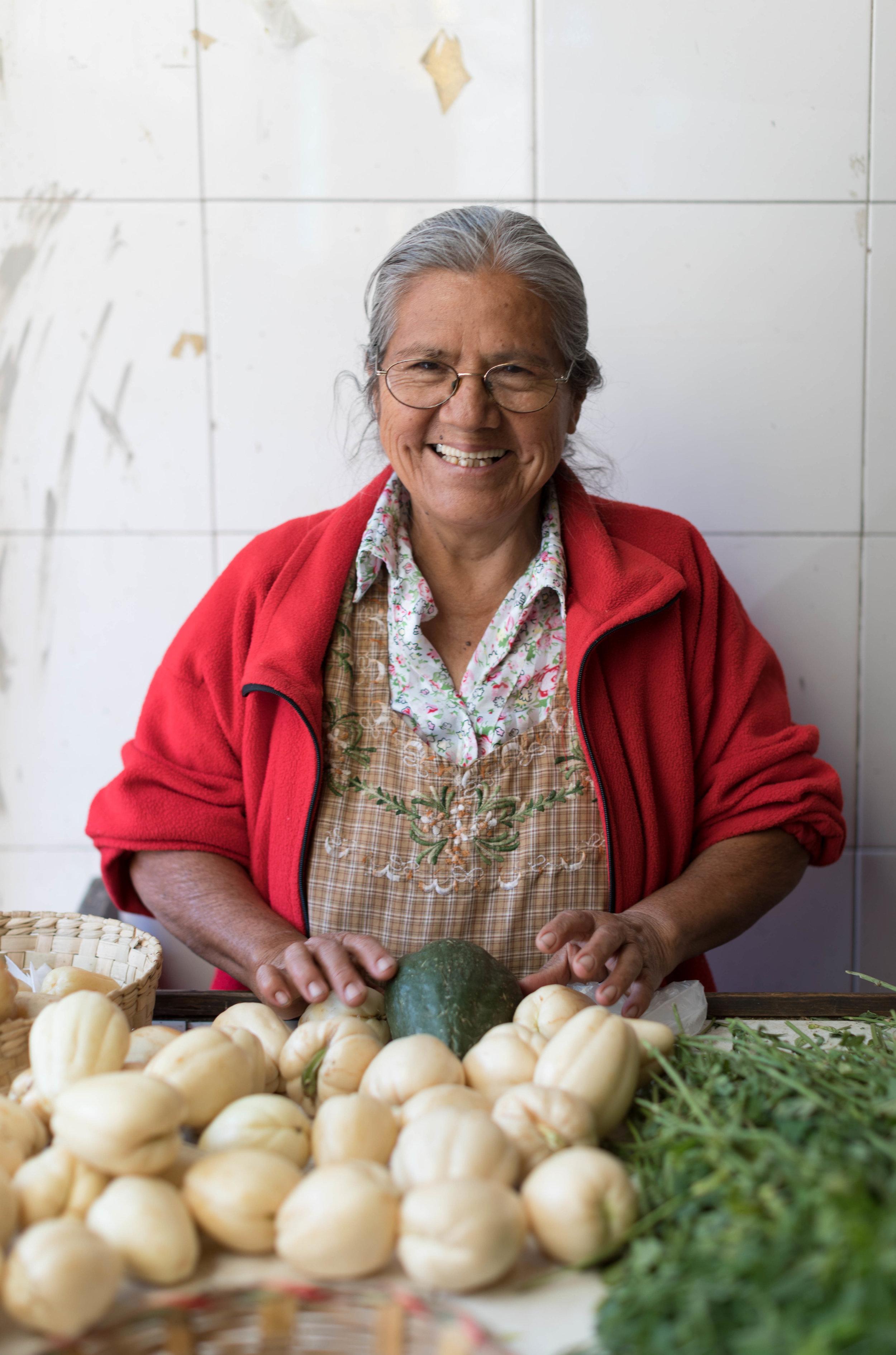 Woman selling chayote and alfalfa at the Mercado de la Merced.