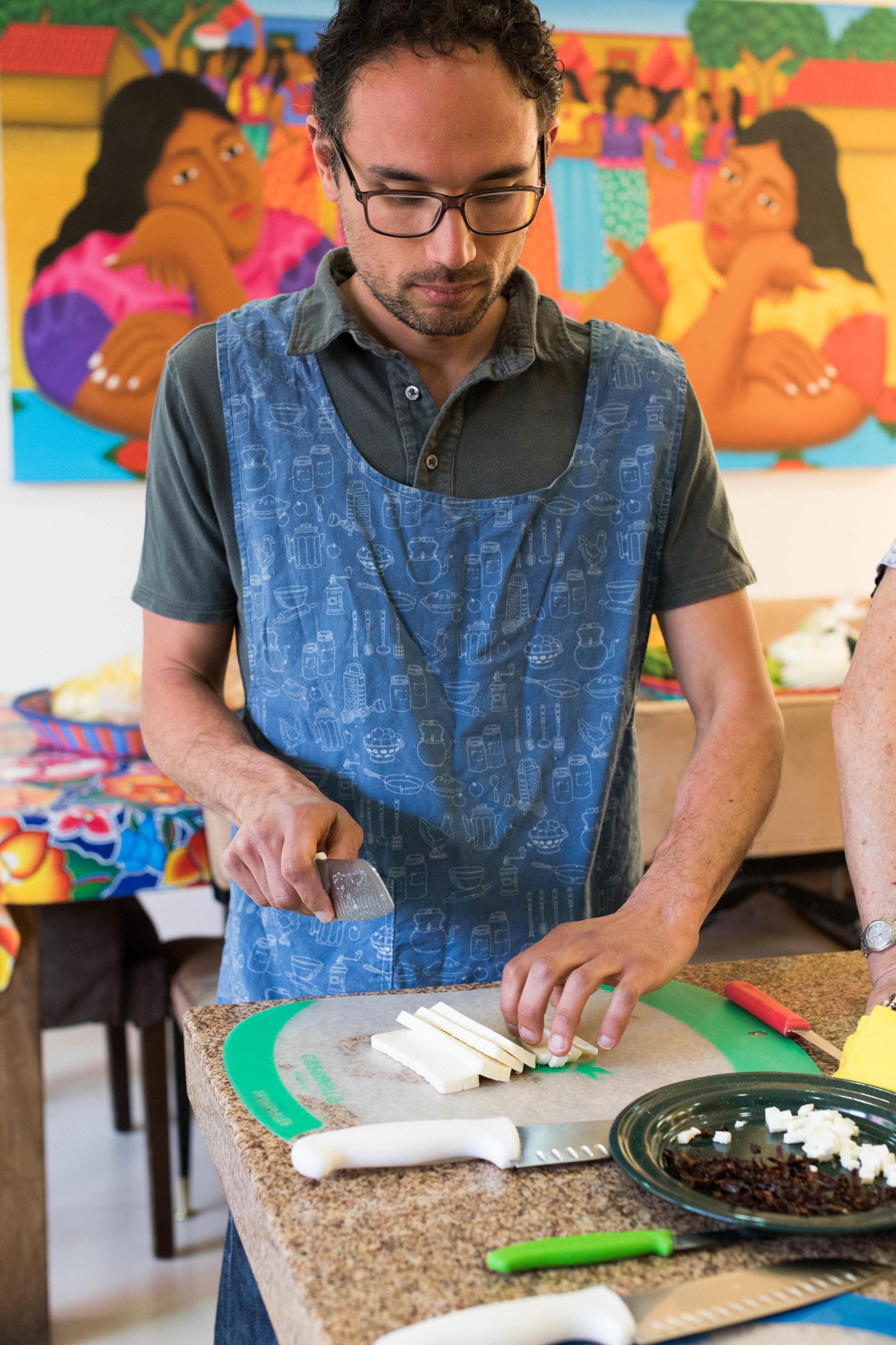 Adam slicing Oaxaca cheese