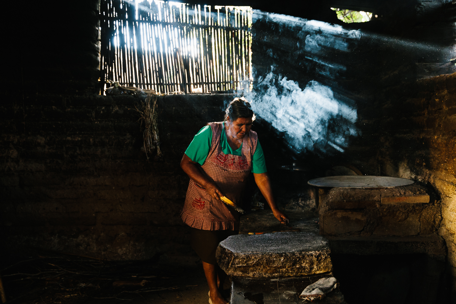 Gloria tending the fire for the comal in her kitchen.