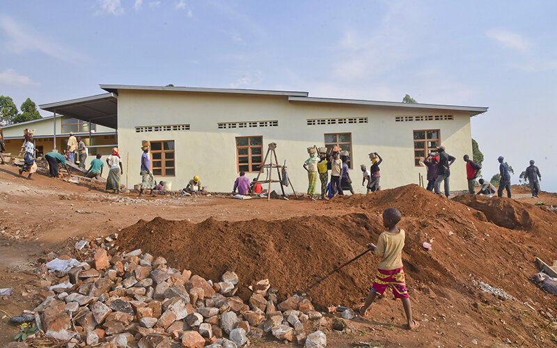 """In 2018, Village Health Works and the Kigutu community came together to build a new school. With their own hands, community members cleared and leveled the land, made bricks and even constructed the furniture. In just three months the new school building went from being a dream to becoming a reality. In September of 2018 the school doors opened with 12 new classrooms, which allows for reduced class sizes.   """"With the new school, we are happy because there has been a significant improvement in terms of infrastructure, increased number of classrooms, and improved hygiene.""""  –Acqueline Niyonzima, School Director"""
