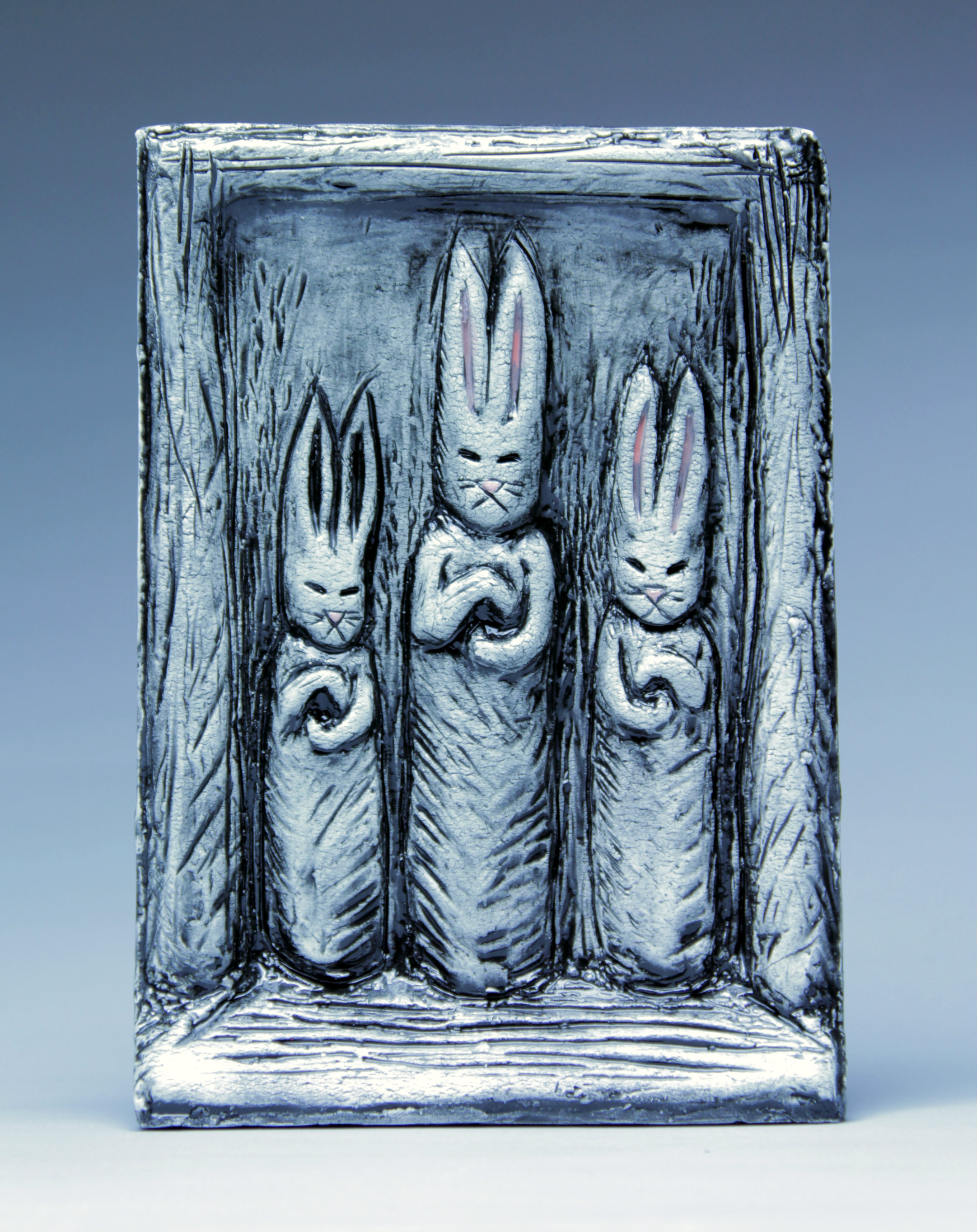 """""""The Three Sisters"""" Clay, Glaze- another iteration of my votive rabbit series. This is a roughly 6 in. x 8 in. ceramic tile that can hang on the wall. I made a mold of my original, then created a few more- including a few that have backs so they can stand alone on a shelf or desk top."""
